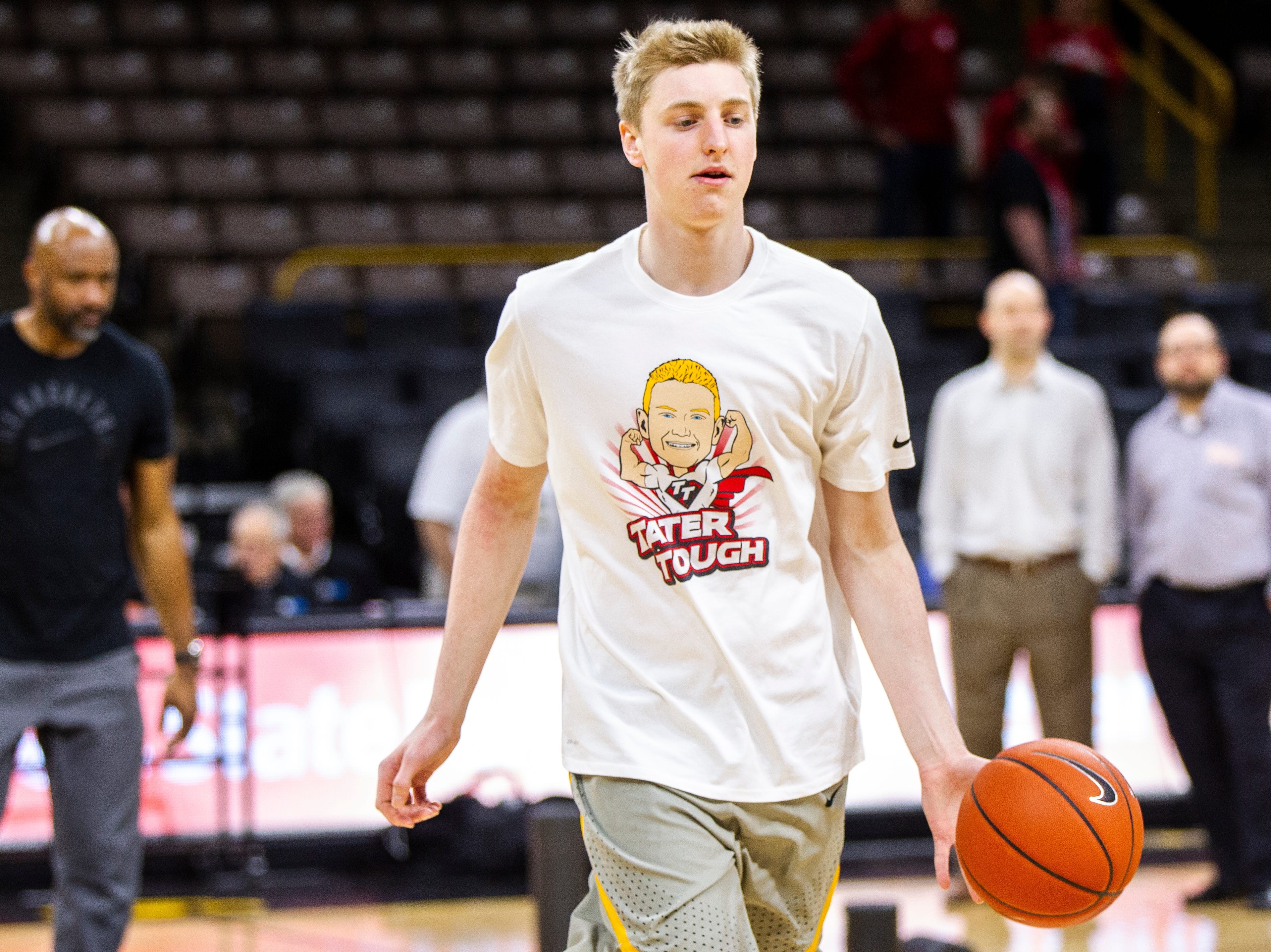 Iowa forward Michael Baer (0) warms up while wearing a shirt featuring a logo for Tate Schaefer, an 11-year-old from Williamsburg who has a tumor in his brain before a NCAA Big Ten Conference men's basketball game on Sunday, Jan. 6, 2019, at the Carver-Hawkeye Arena in Iowa City, Iowa.