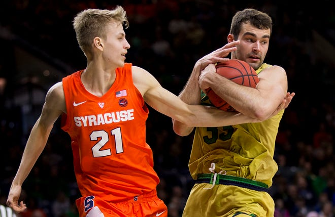 Notre Dame's John Mooney (33) grabs a rebound next to Syracuse's Marek Dolezaj (21) during the first half of an NCAA college basketball game Saturday, Jan. 5, 2019, in South Bend, Ind. (AP Photo/Robert Franklin)