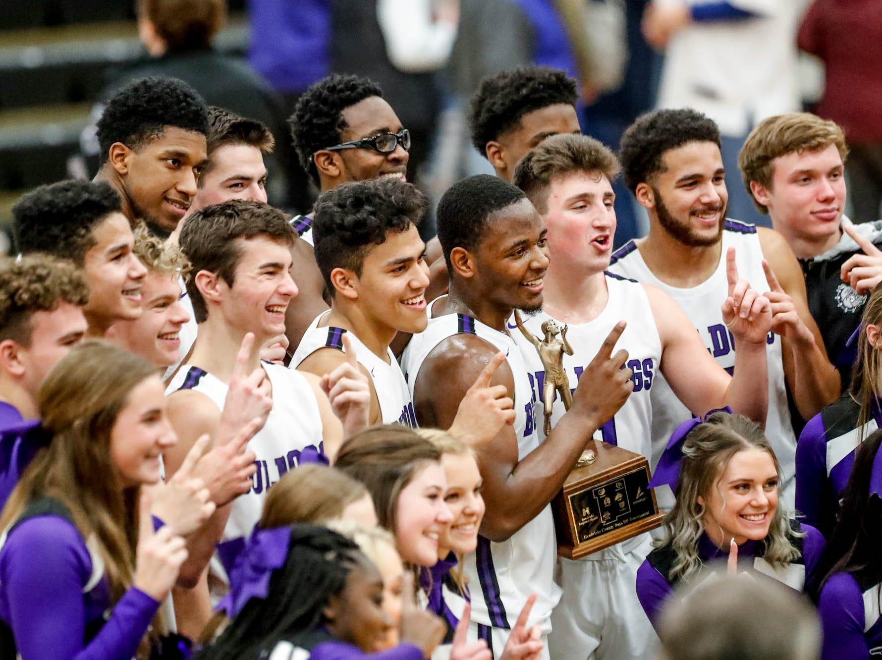 Brownsburg players pose for photos after winning the 2019 Hendricks County Basketball Tournament game between the Avon High School boys varsity basketball team and Brownsburg High School, held at Cascade High School on Saturday, Jan. 5, 2019.