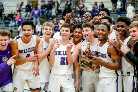 Brownsburg players pose for photos after winning the 2019 Hendricks County Basketball Tournament game between the Avon High School boys varsity basketball team and Brownsburg High School, held at Cascade High School on Saturday, Jan. 5, 2019.