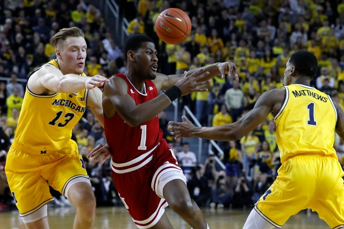 Michigan guard Charles Matthews, right, knocks the ball away from Indiana guard Aljami Durham, center, as Michigan's Ignas Brazdeikis (13) defends in the first half of an NCAA college basketball game in Ann Arbor, Mich., Sunday, Jan. 6, 2019.