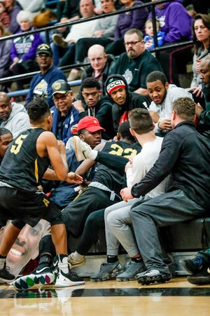 Avon High School's Wendell DeMyers chases a ball in to the stands, and is helped out by team mate Avon High School's Le'Angelo Saravie (5), during the 2019 Hendricks County Basketball Tournament game between the Avon High School boys varsity basketball team and Brownsburg High School, held at Cascade High School on Saturday, Jan. 5, 2019.