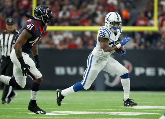 Indianapolis Colts running back Marlon Mack (25) runs away from Houston Texans inside linebacker Zach Cunningham (41) during their AFC Wild Card playoff game at NRG Stadium in Houston, TX., on Saturday, Jan. 5, 2019. The Indianapolis Colts defeated the Houston Texans 21-7