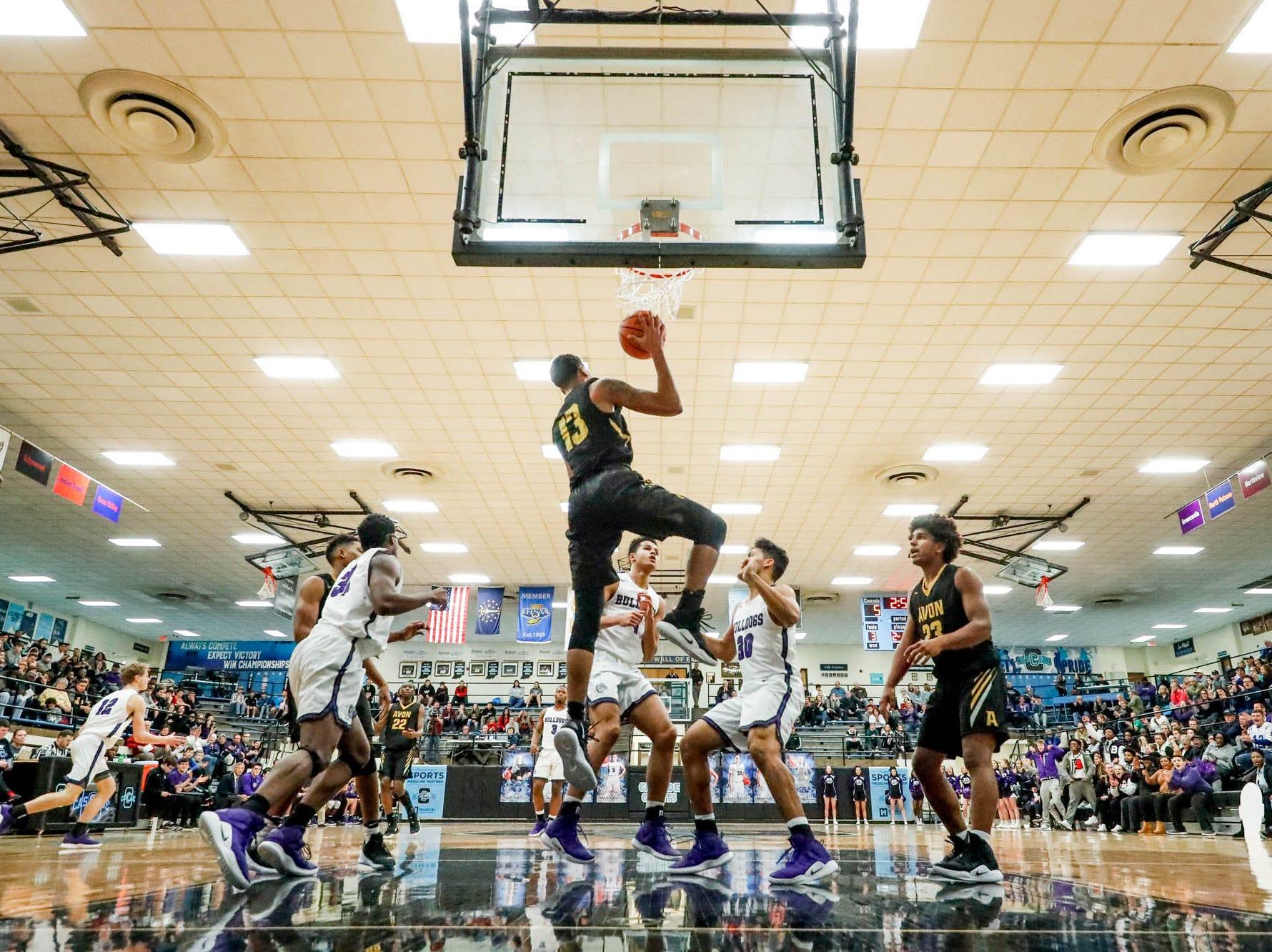 Avon High School's Jayden Baylor (13), snatches a rebound during the 2019 Hendricks County Basketball Tournament game between the Avon High School boys varsity basketball team and Brownsburg High School, held at Cascade High School on Saturday, Jan. 5, 2019.