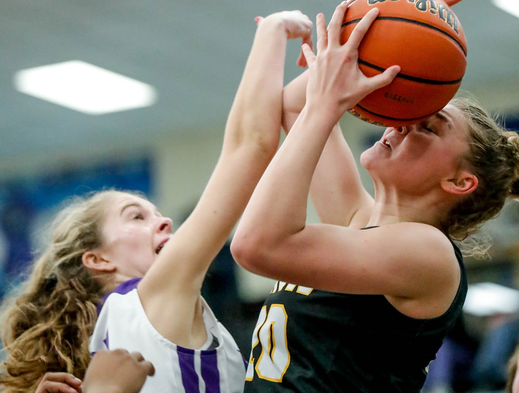 Avon High School's forward Alex Richard (20), takes a ball to the face during a 2019 Hendricks County Basketball Tournament game between the Avon High School girls varsity basketball team and Brownsburg High School, held at Cascade High School on Saturday, Jan. 5, 2019. Brownsburg High School's guard Victoria Olmstead (21), left.
