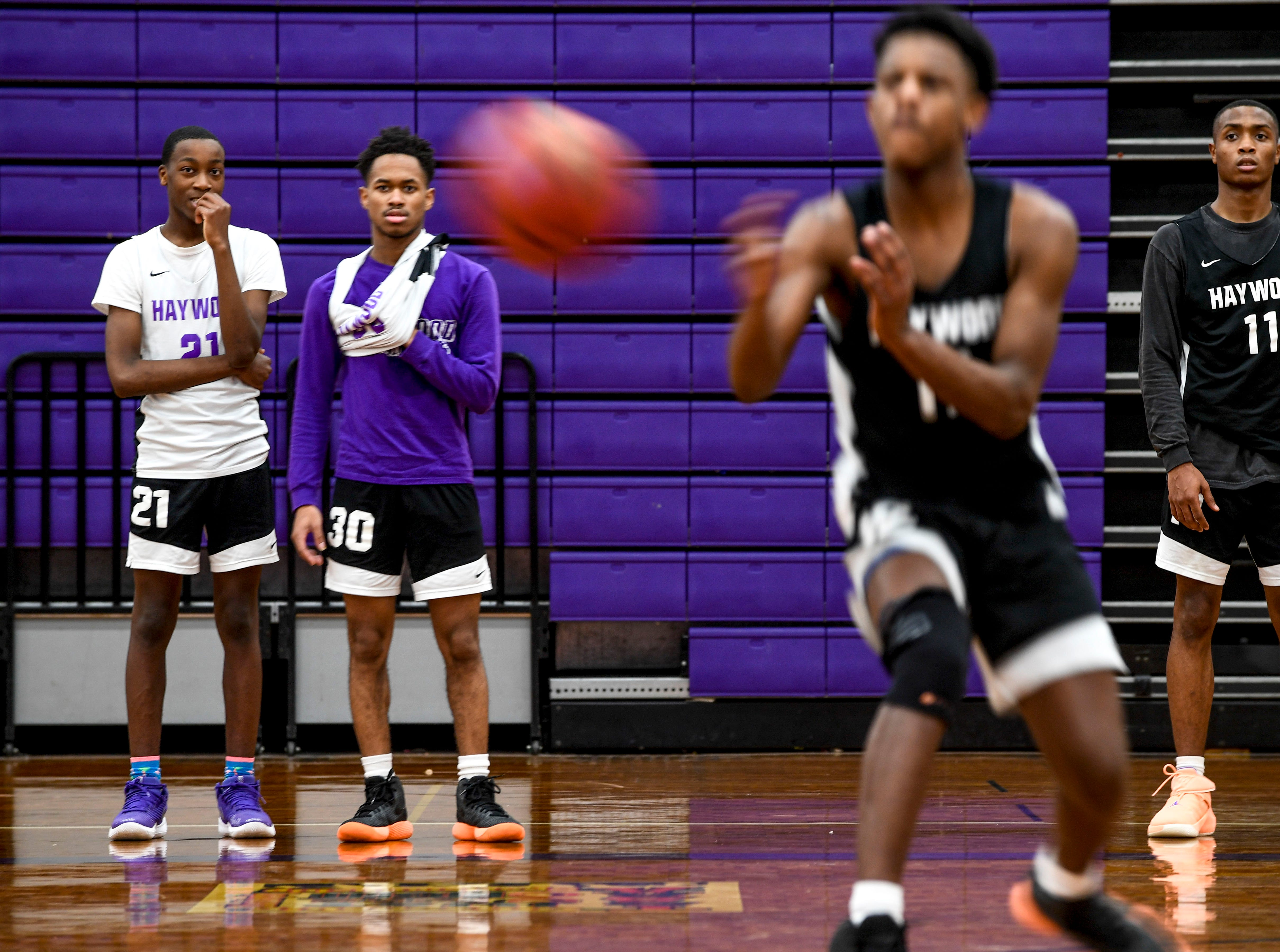 Players watch from the sidelines while their teammates practice a 5v5 game during basketball practice at Haywood High School in Brownsville, Tenn., on Wednesday, Jan. 2, 2019.