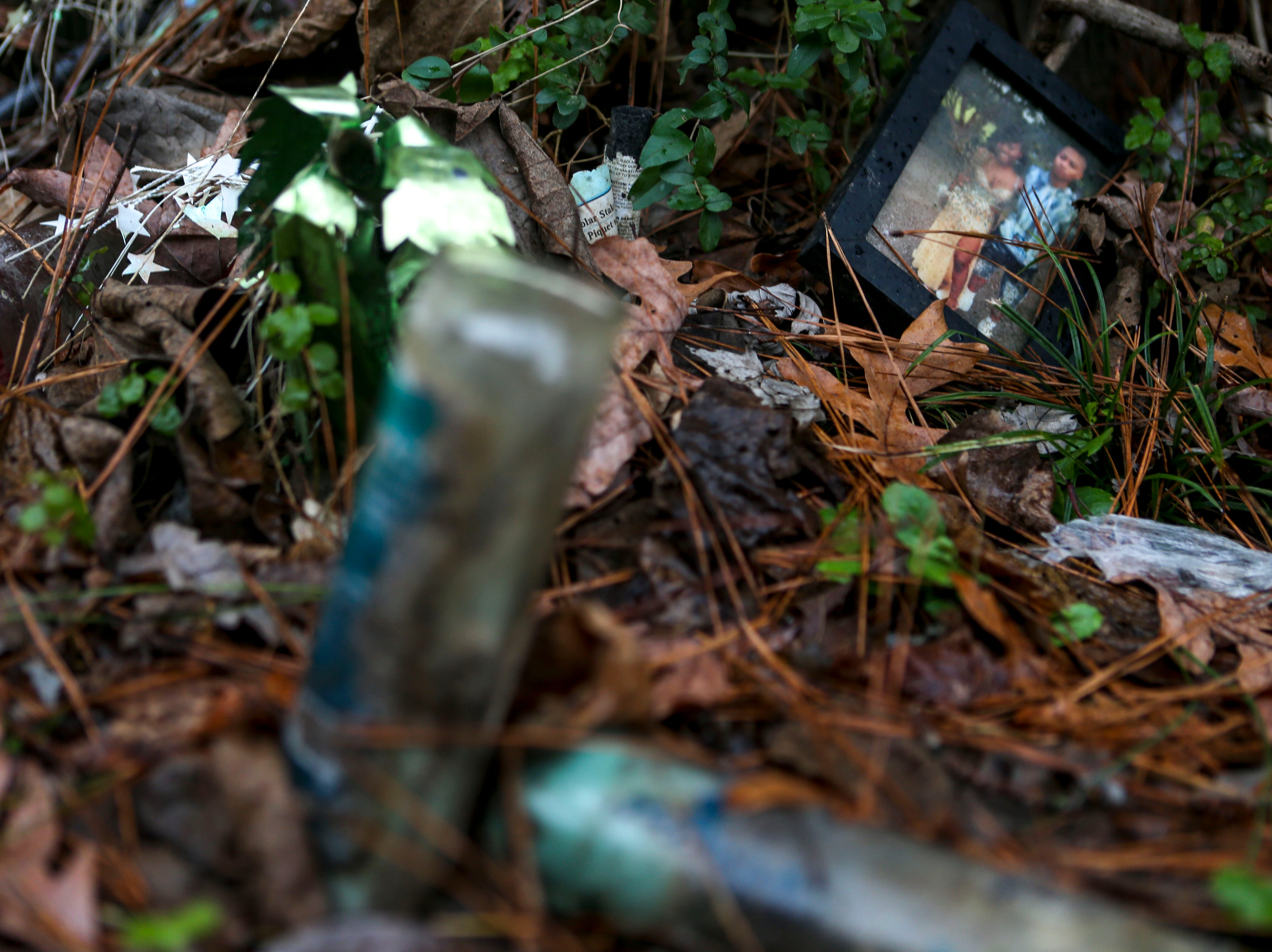 A framed picture that shows Kentavious Wilson and a friend  is placed at the base of a tree near the location where Wilson was killed last January at 600 block of Coach Street in Brownsville, Tenn., on Wednesday, Jan. 2, 2019.