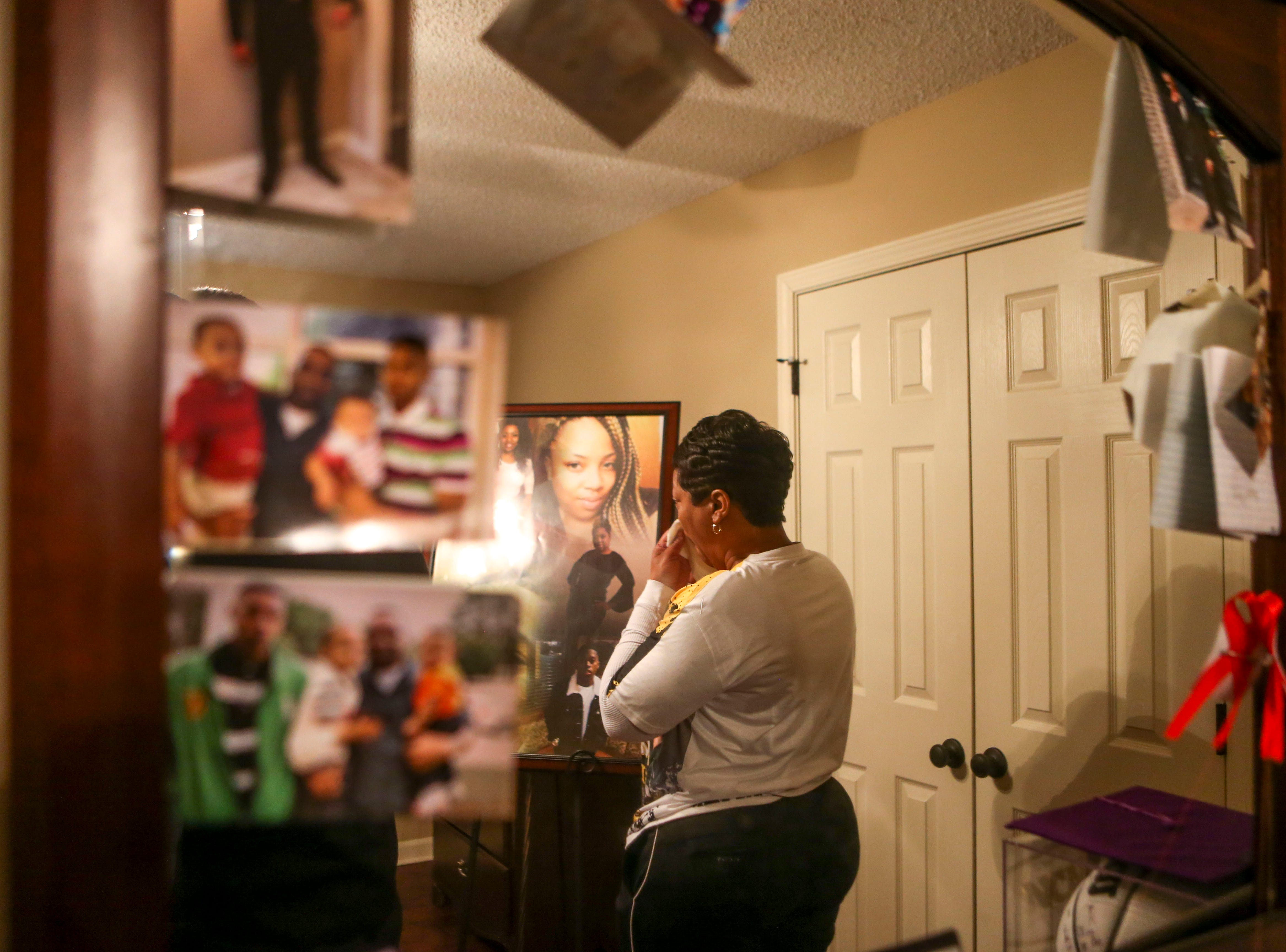 Kemmeka Currie blows her nose in the room of her deceased son, Kentavious Wilson, where she has set up a number of his belongings and photos of him at the Currie's home in Brownsville, Tenn., on Wednesday, Jan. 2, 2019.