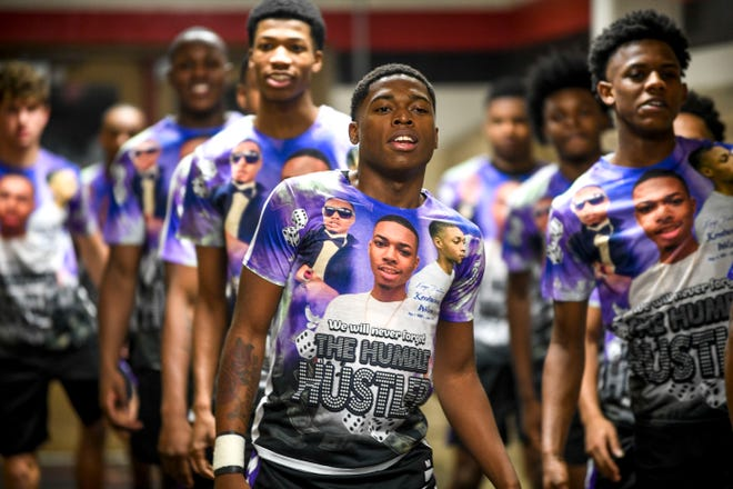 Haywood's Kyron Stocking leads his team in warm-ups Saturday before a game against South Side. The Haywood players wore shirts with an image of Stocking's brother, Kentavious Wilson, a former Haywood player who was killed last year.