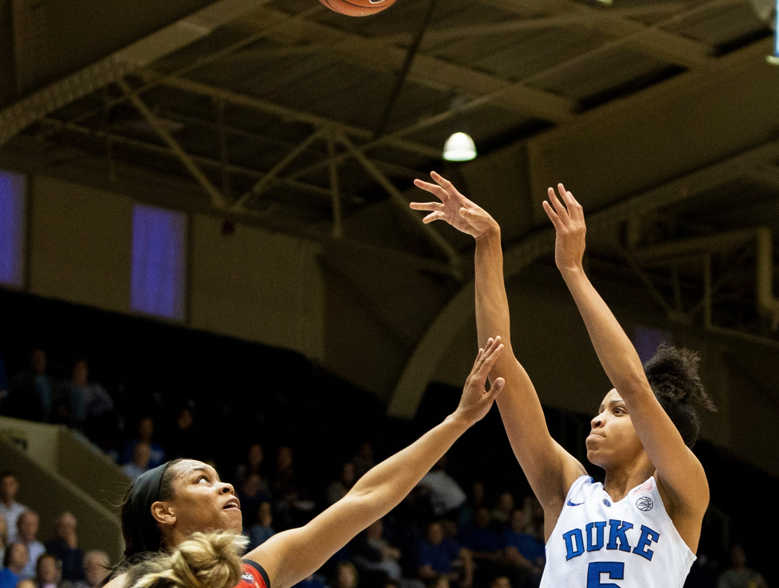 Duke's Leaonna Odom, right, attempts a shot over Louisville's Asia Durr, left, during the second half of an NCAA college basketball game in Durham, N.C., Sunday, Jan. 6, 2019.