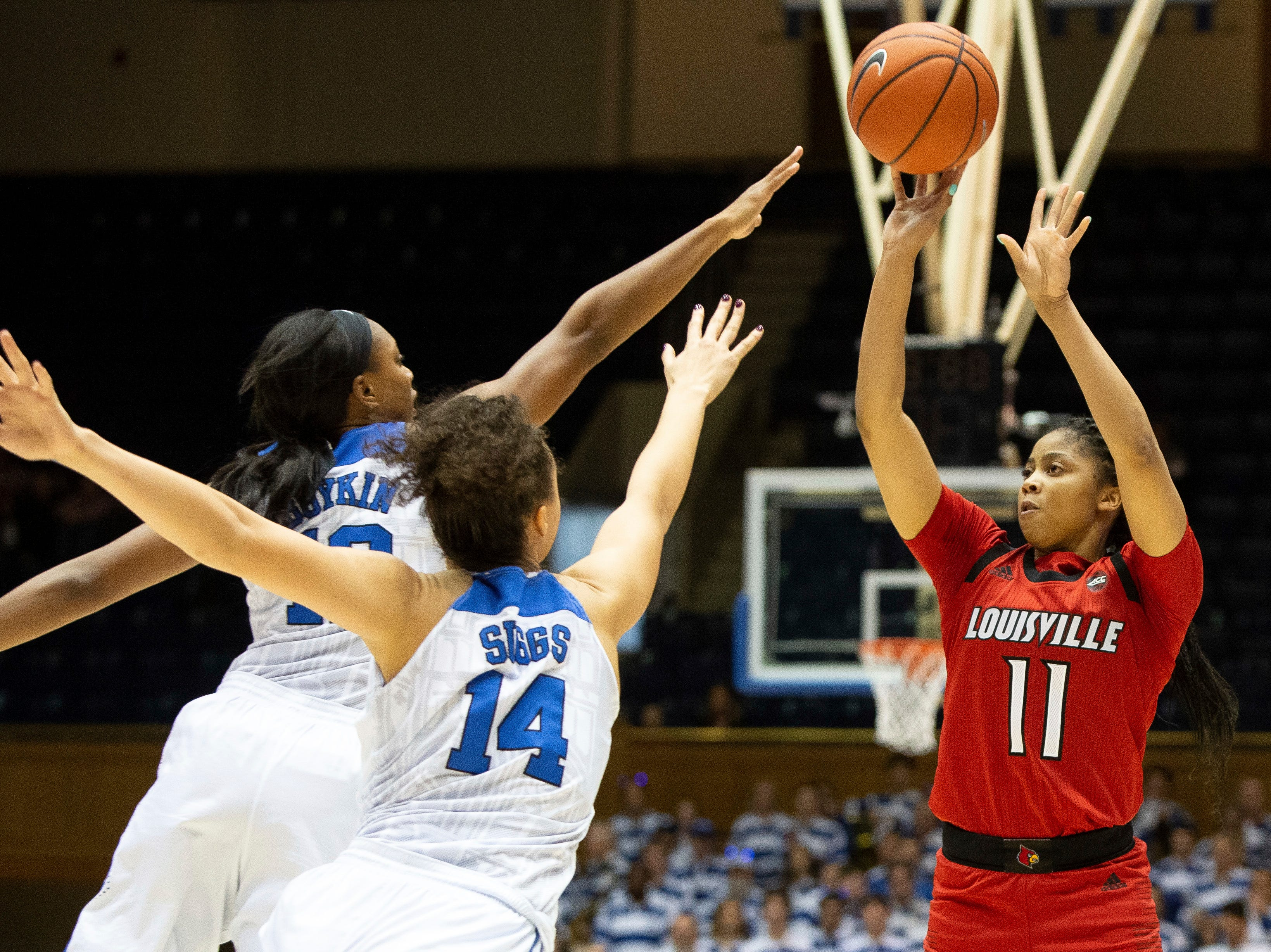Louisville's Arica Carter, right, attempts a shot over Duke's Faith Suggs, center, and Mikayla Boykin, left, during the first half of an NCAA college basketball game in Durham, N.C., Sunday, Jan. 6, 2019.