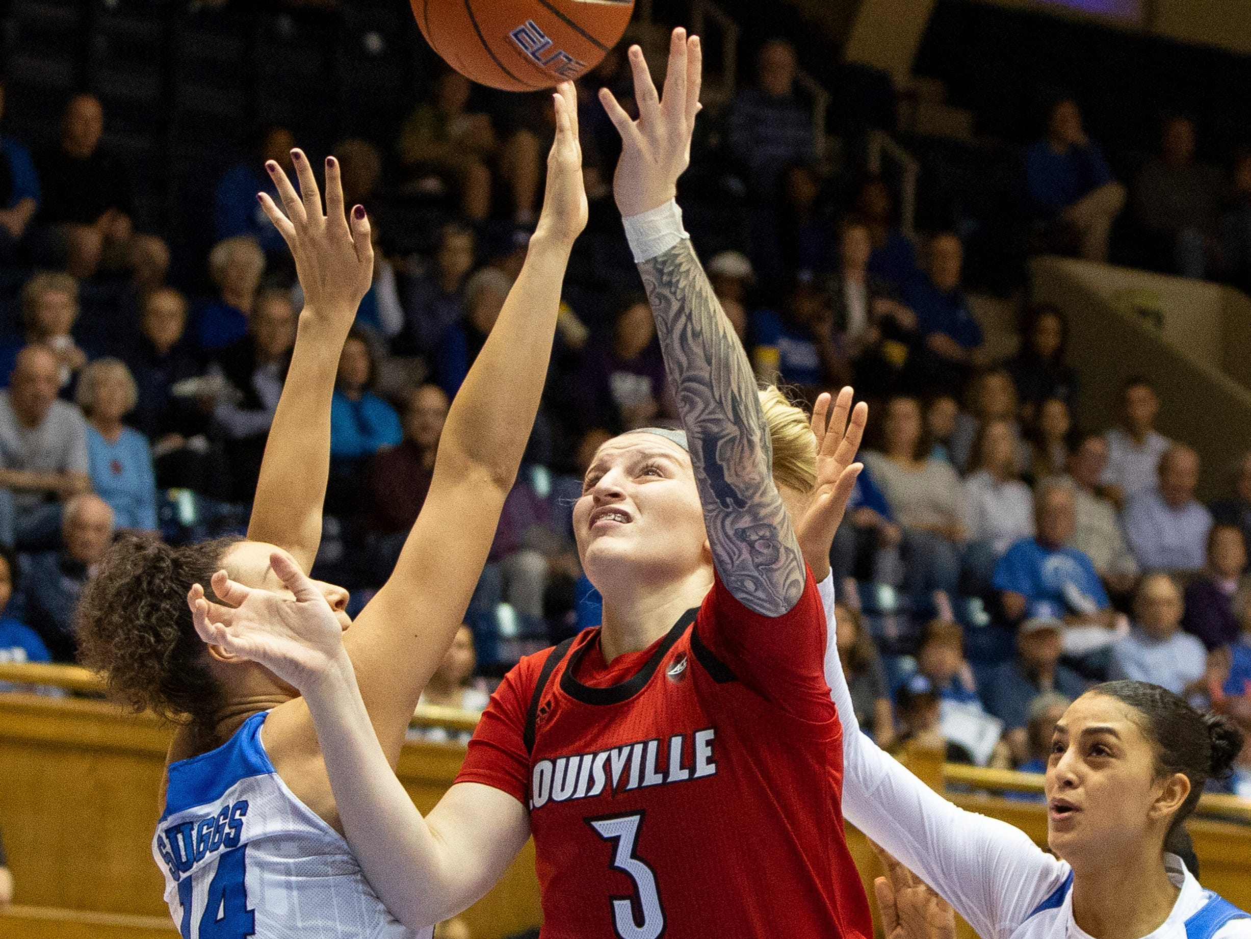 Louisville's Sam Fuehring (3) attempts a shot between Duke's Faith Suggs (14) and Jade Williams (25) during the first half of an NCAA college basketball game in Durham, N.C., Sunday, Jan. 6, 2019.
