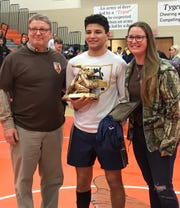Bill Flanegan Jr. and his daughter Bri flank Norwalk's Ethan Hernandez, winner of the Bill Flanegan Outstanding Wrestler award at the 57th J.C. Gorman Invitational