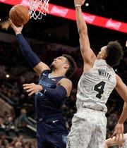 Memphis Grizzlies' Dillon Brooks, left, shoots against San Antonio Spurs' Derrick White during the first half of an NBA basketball game, Saturday, Jan. 5, 2019, in San Antonio. (AP Photo/Darren Abate)