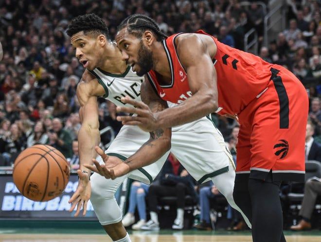 Bucks forward Giannis Antetokounmpo tries to steal the ball from Toronto Raptors forward Kawhi Leonard.