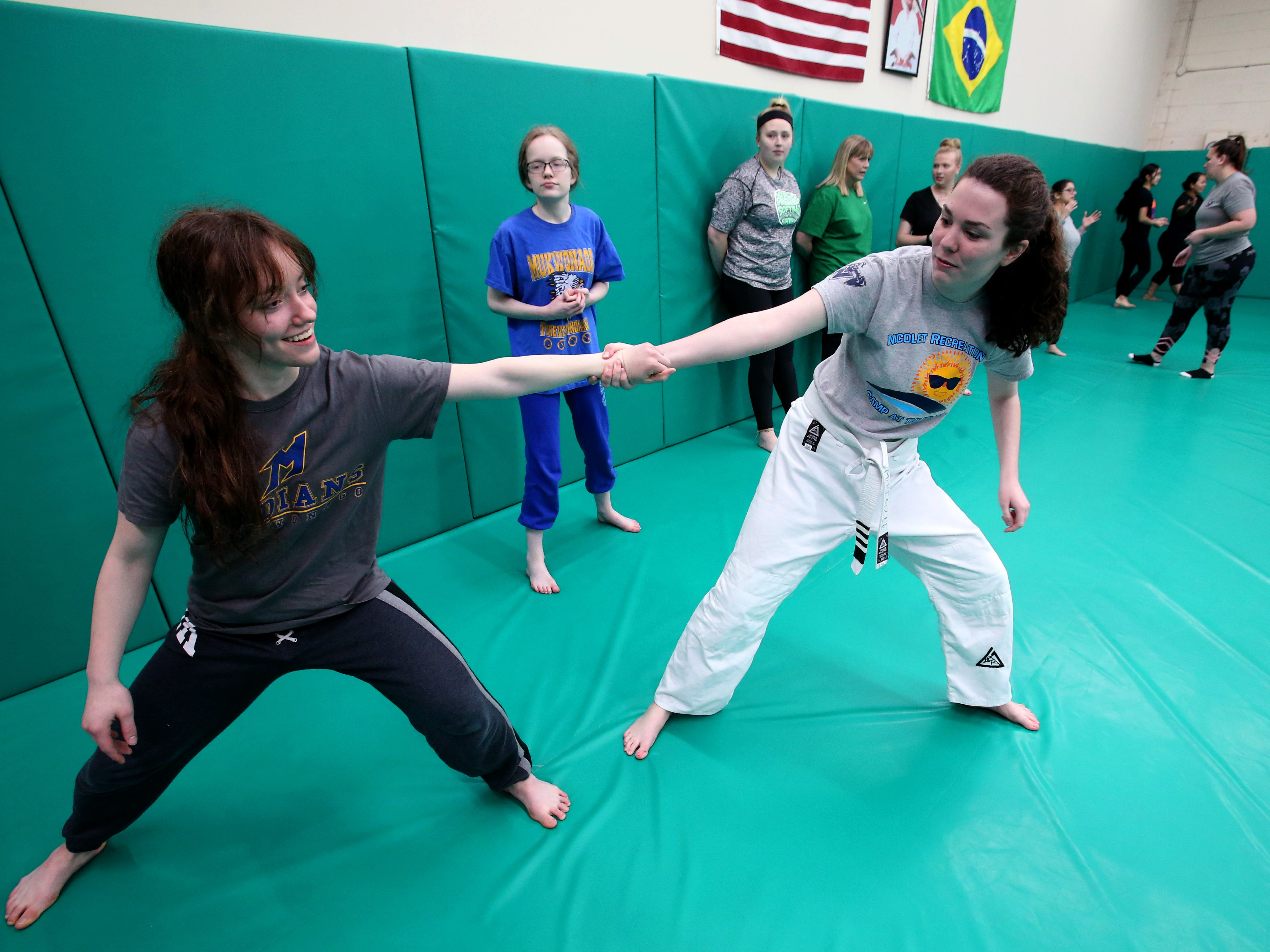 Morgan (left) and Maddy Vele of Mukwonago practice with McKenzie Clark (right) of Bayside a battle base stance if pulled or pushed during a self defense workshop for first-time students at Gracie Jiu-Jitsu Milwaukee in Wauwatosa on Jan. 5.