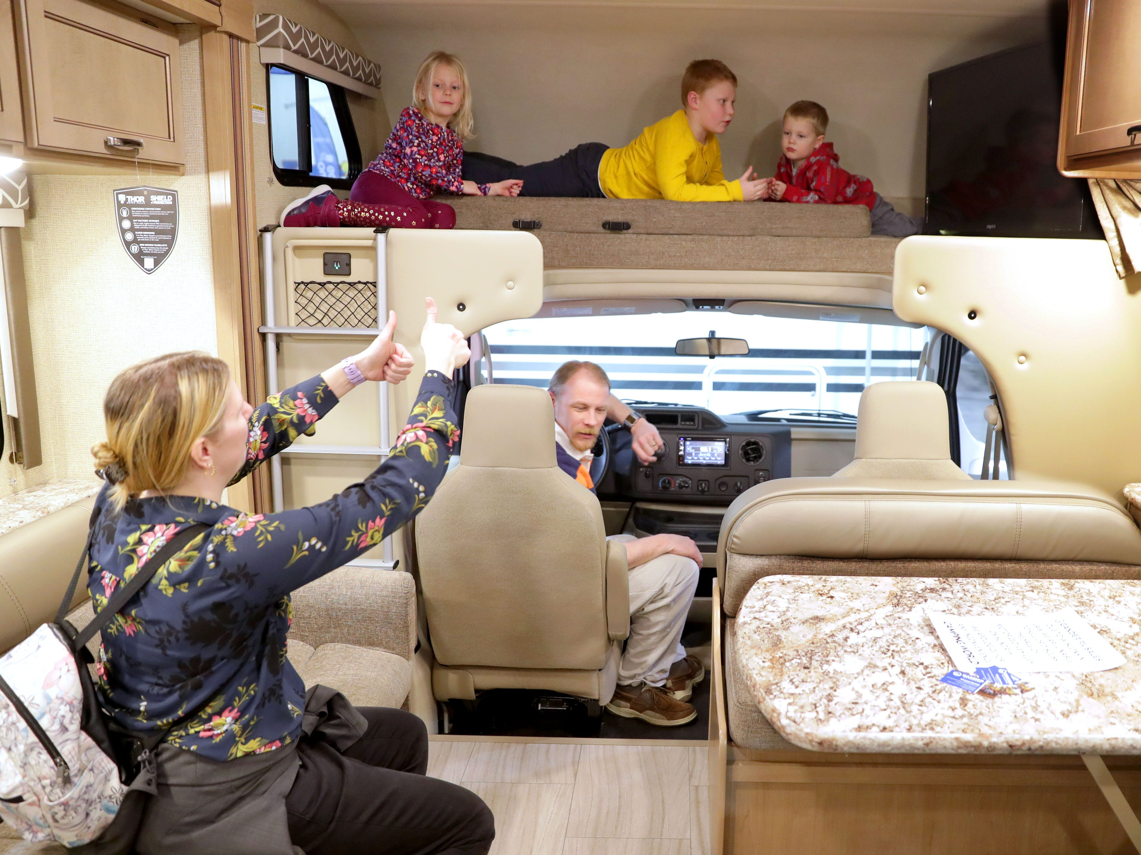 Marlaina Sheahan, 4, and her brothers Carson, 7, and Dennis, 2, sit in the bunk area as their mother, Amy Sheahan gives the thumbs-up while her husband, Brian, sits in the driver's seat of a 2019 Motor Coach Daybreak that lists for $84,999. While the family didn't purchase the RV, they enjoyed looking at the assortment during the 2019 Wisconsin RV Show at the Wisconsin Center in Milwaukee on Sunday. The show ran through Sunday and included RVs, information on campsites, tow vehicle seminars and entertainment.