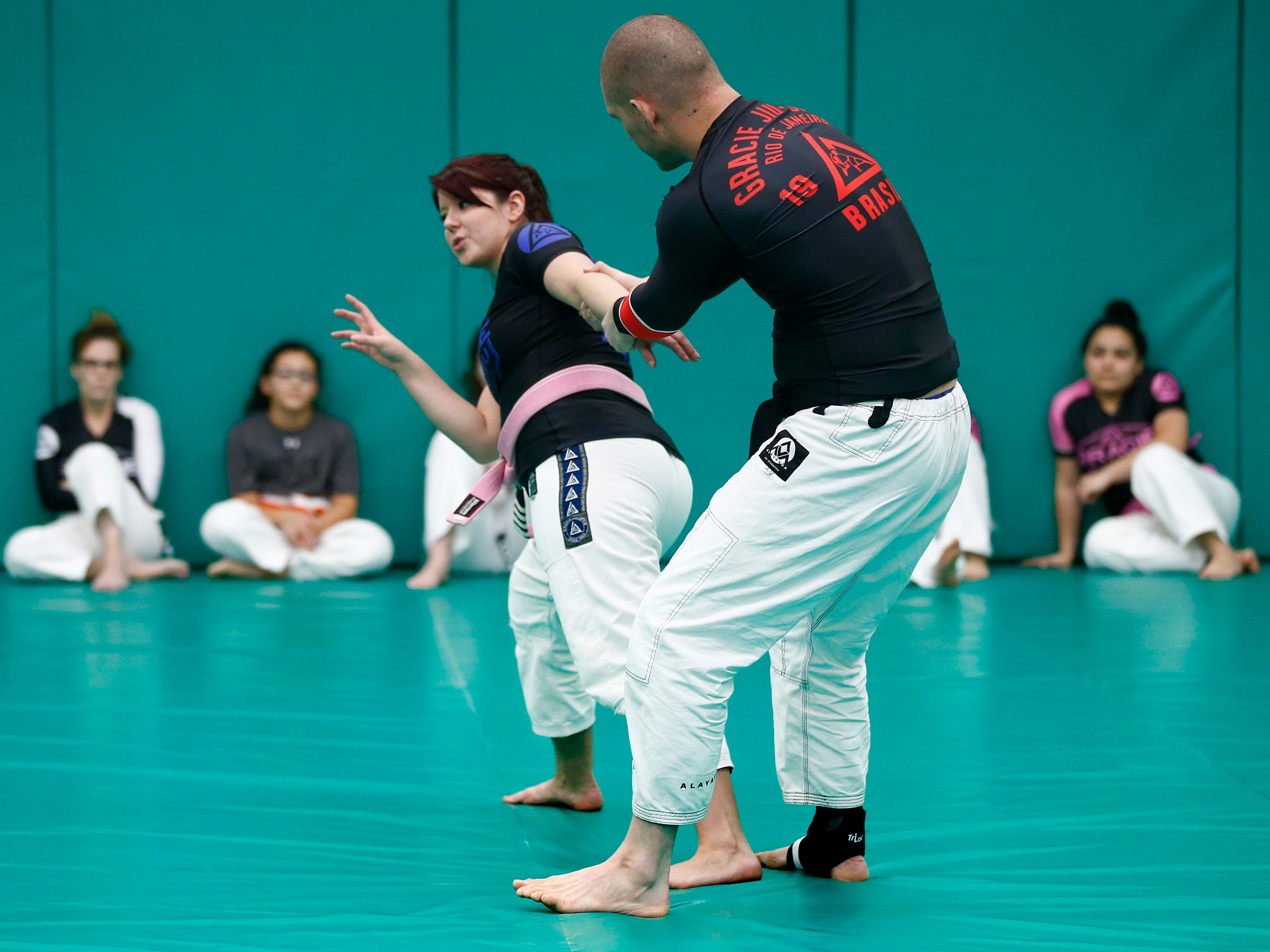 Danielle Rabideaux and Skye Middleton demonstrate a battle base stance during a self defense workshop for first-time students at Gracie Jiu-Jitsu Milwaukee in Wauwatosa on Jan. 5.