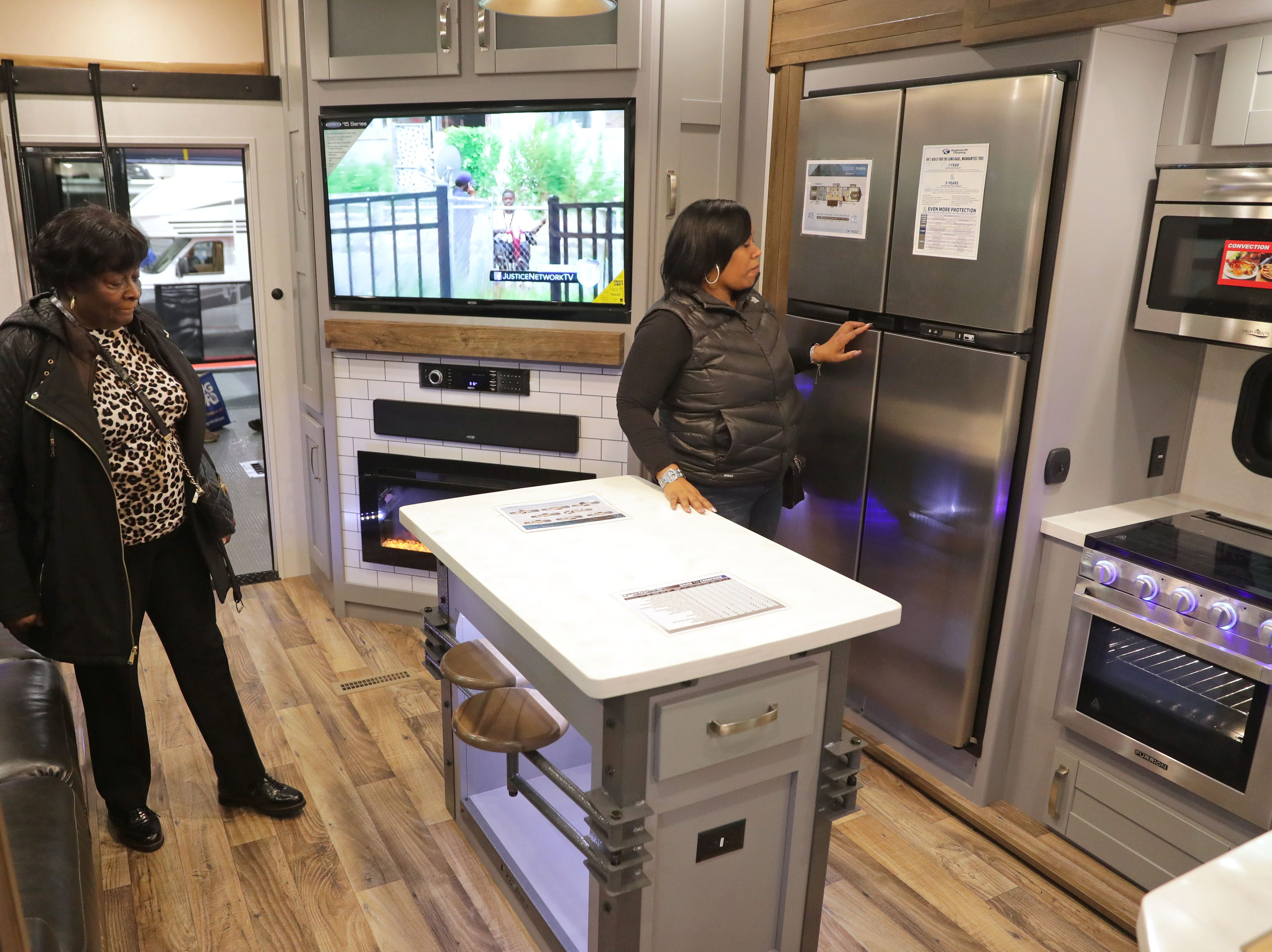 Johnnie Scott (left) of Glendale and her daughter, Kaelin Whitley, of Milwaukee check out the interior kitchen area of the 2019 keystone Fuzion, which lists for $69,999.
