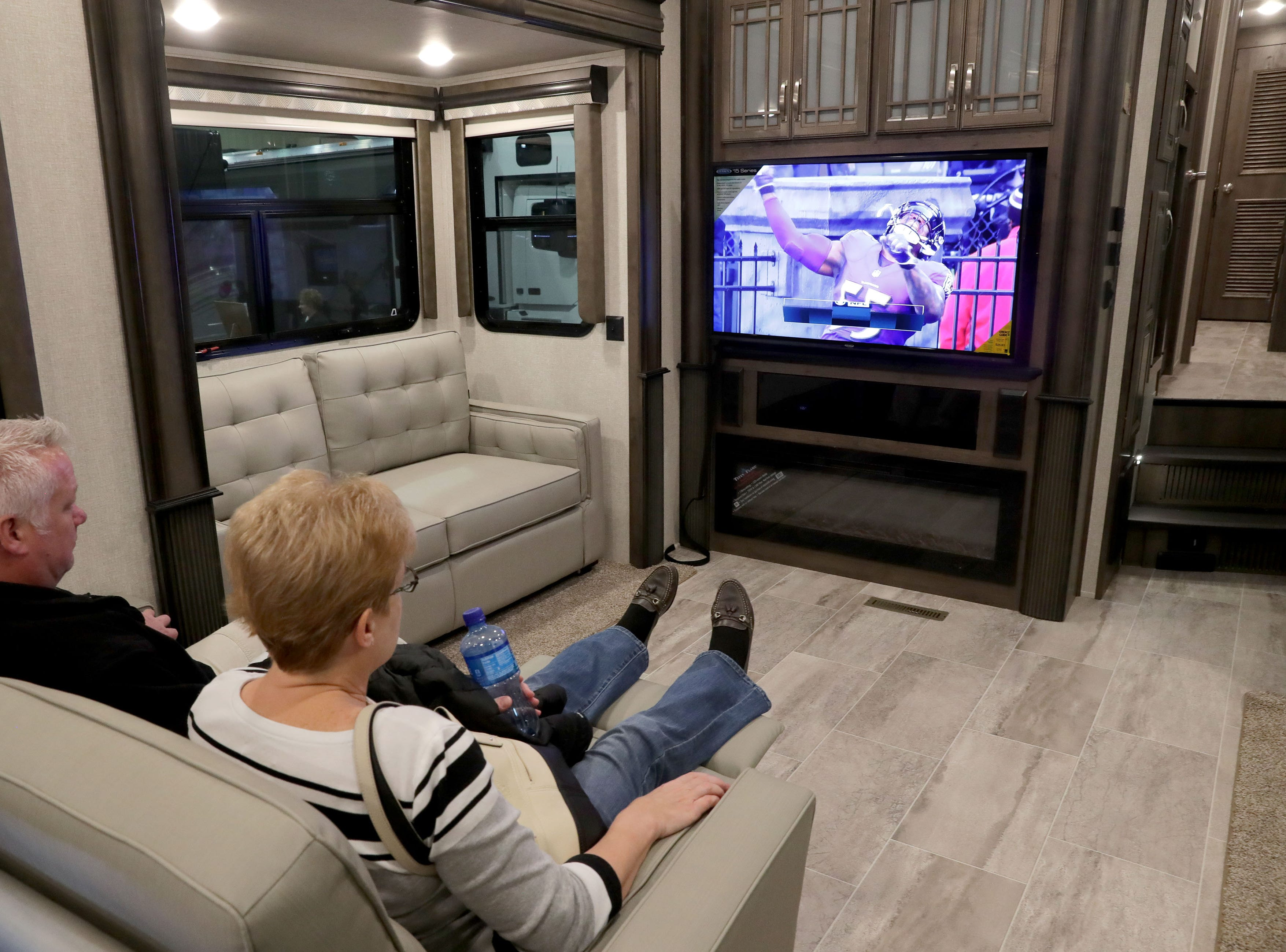 A couple relax in reclining chairs while watching TV in this 2019 Keystone Montana that lists for $63,999.
