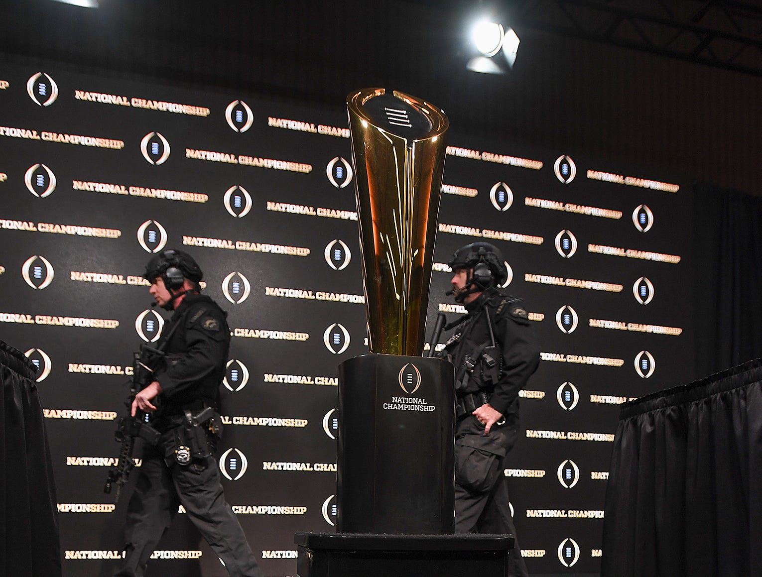 San Jose police walk by the championship trophy before the College Football Playoff Championship coaches press conference in San Jose, California January 6, 2019.
