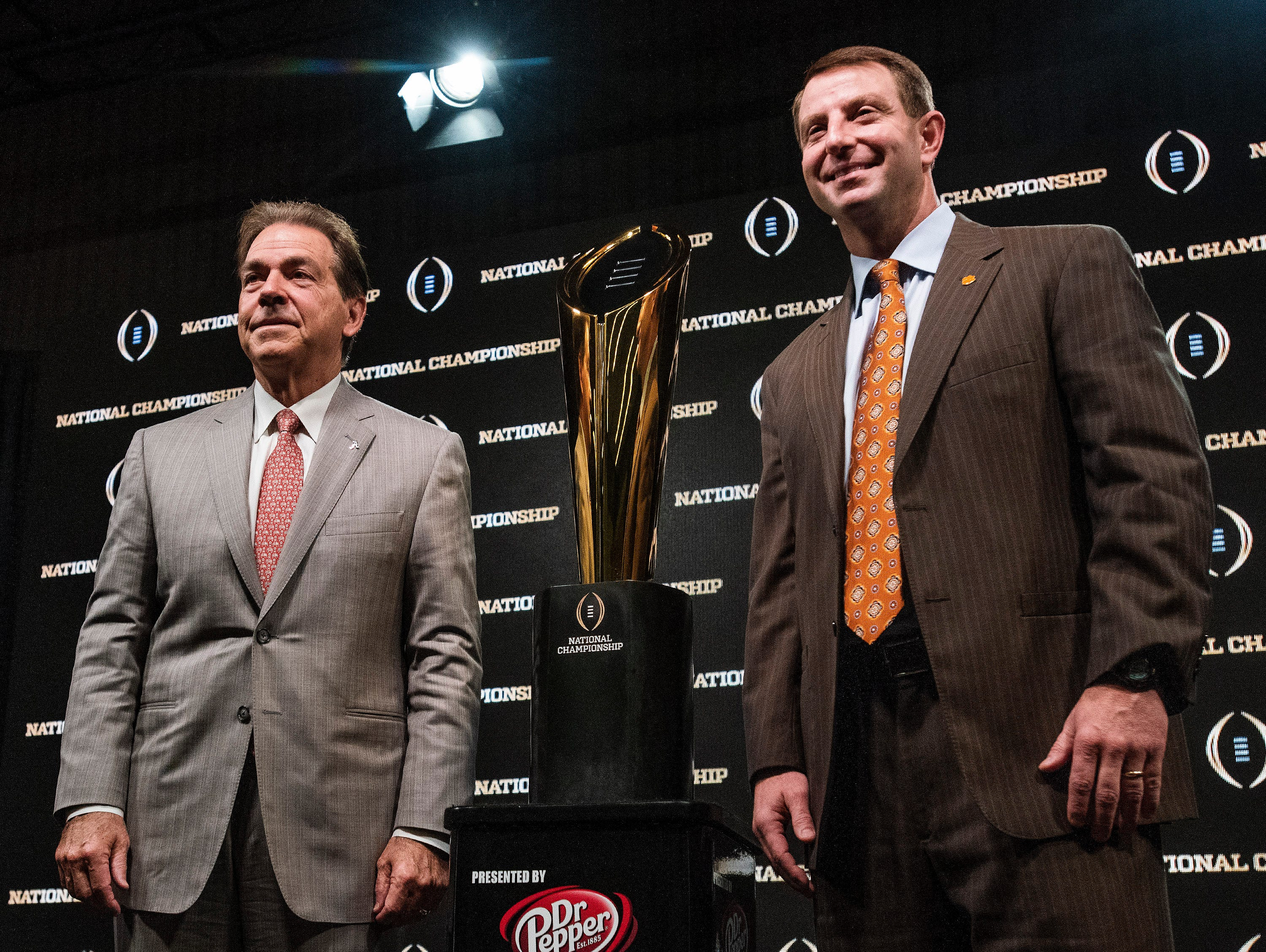 Alabama head coach Nick Sabanand Clemson head coach Dabo Swinney  pose with the trophy during the College Football National Championship coaches press conference in San Jose, Ca., on Sunday January 6, 2019.
