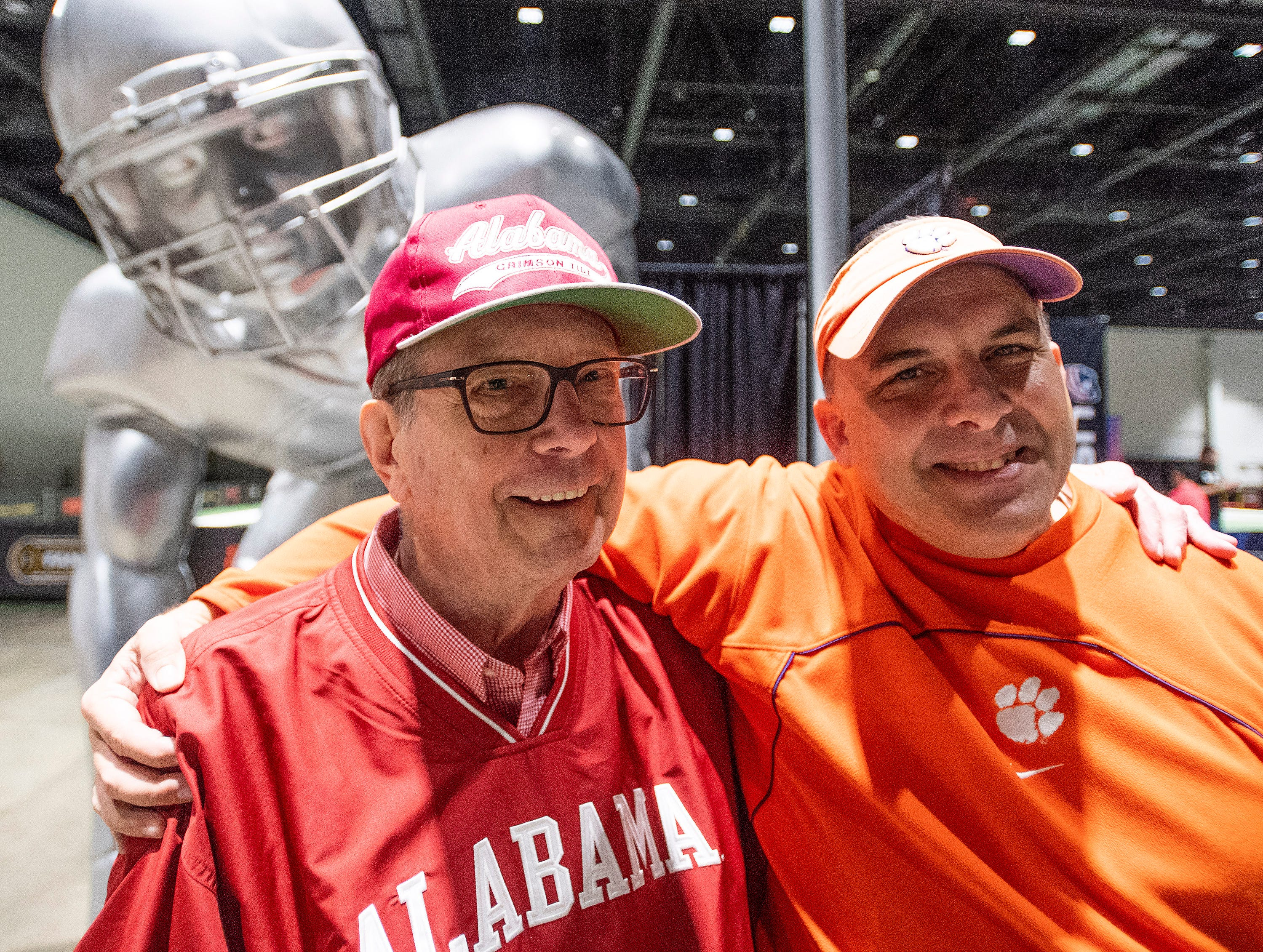 Alabama fan Charles Edgar, left, and his Clemson fan son Glen Adair, right, pose together at Playoff Fan Central at the College Football National Championship in San Jose, Ca., on Sunday January 6, 2019.