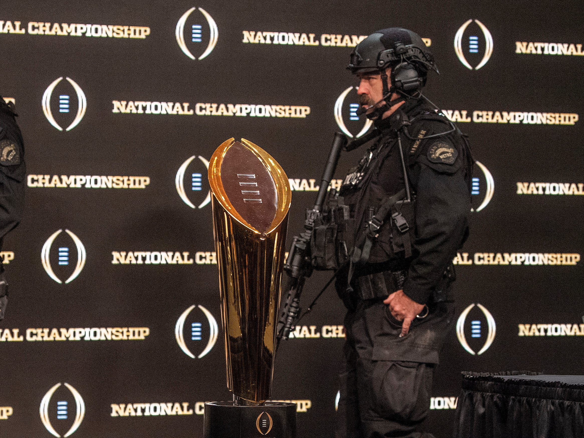 Armed guards walk past the National Championship Trophy before the College Football National Championship coaches press conference in San Jose, Ca., on Sunday January 6, 2019.