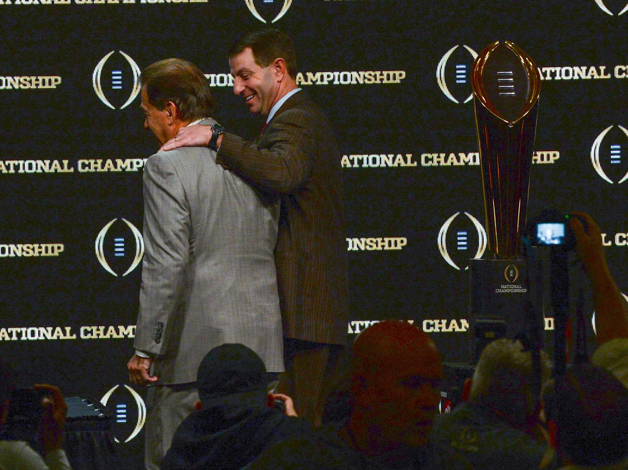 Alabama coach Nick Saban, left, and Clemson Head Coach Dabo Swinney walk off stage together after posing with the championship trophy during the College Football Playoff Championship coaches press conference in San Jose, California January 6, 2019.