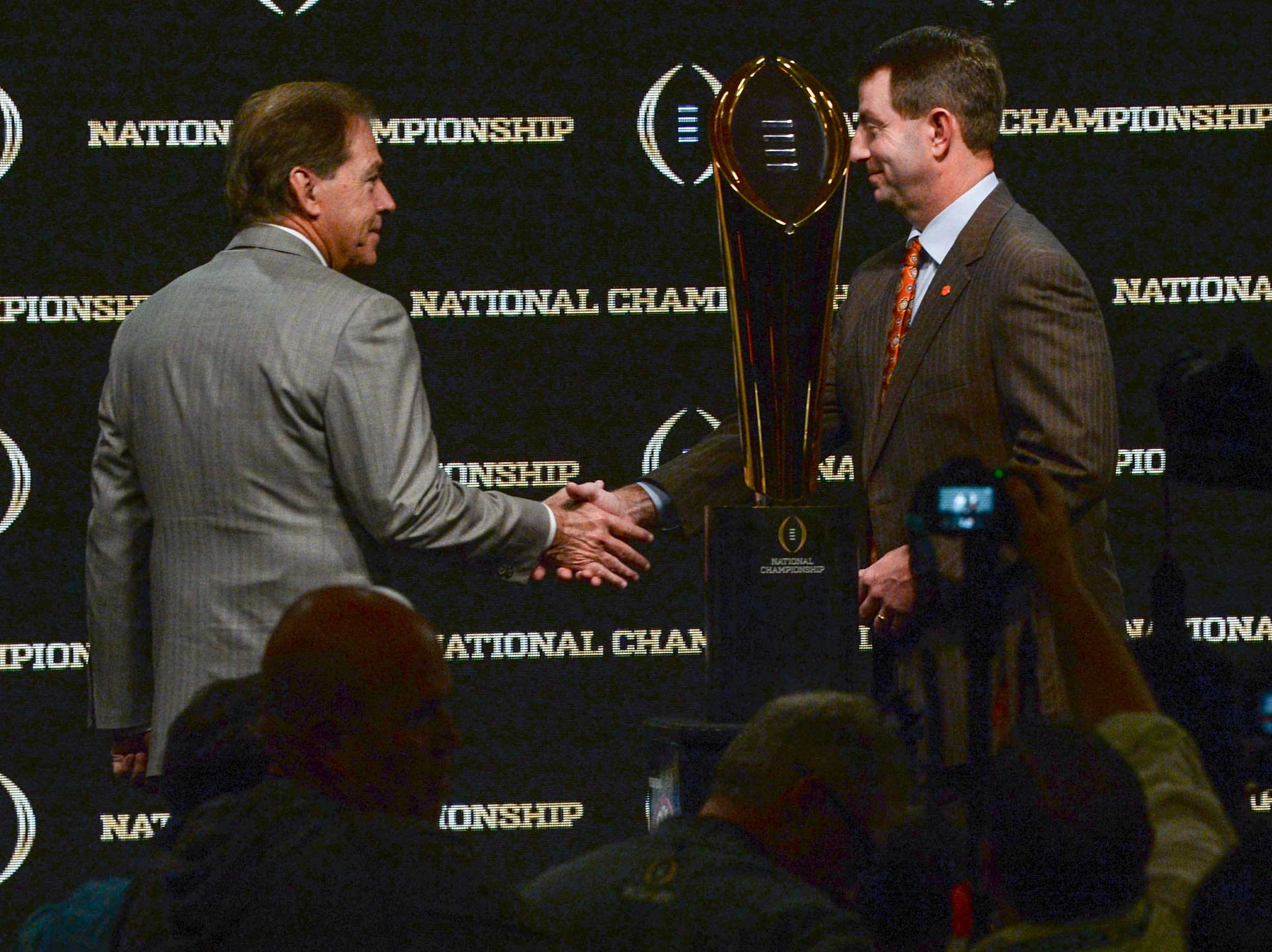 Alabama coach Nick Saban, left, and Clemson Head Coach Dabo Swinney shake hands after posing with the championship trophy during the College Football Playoff Championship coaches press conference in San Jose, California January 6, 2019.