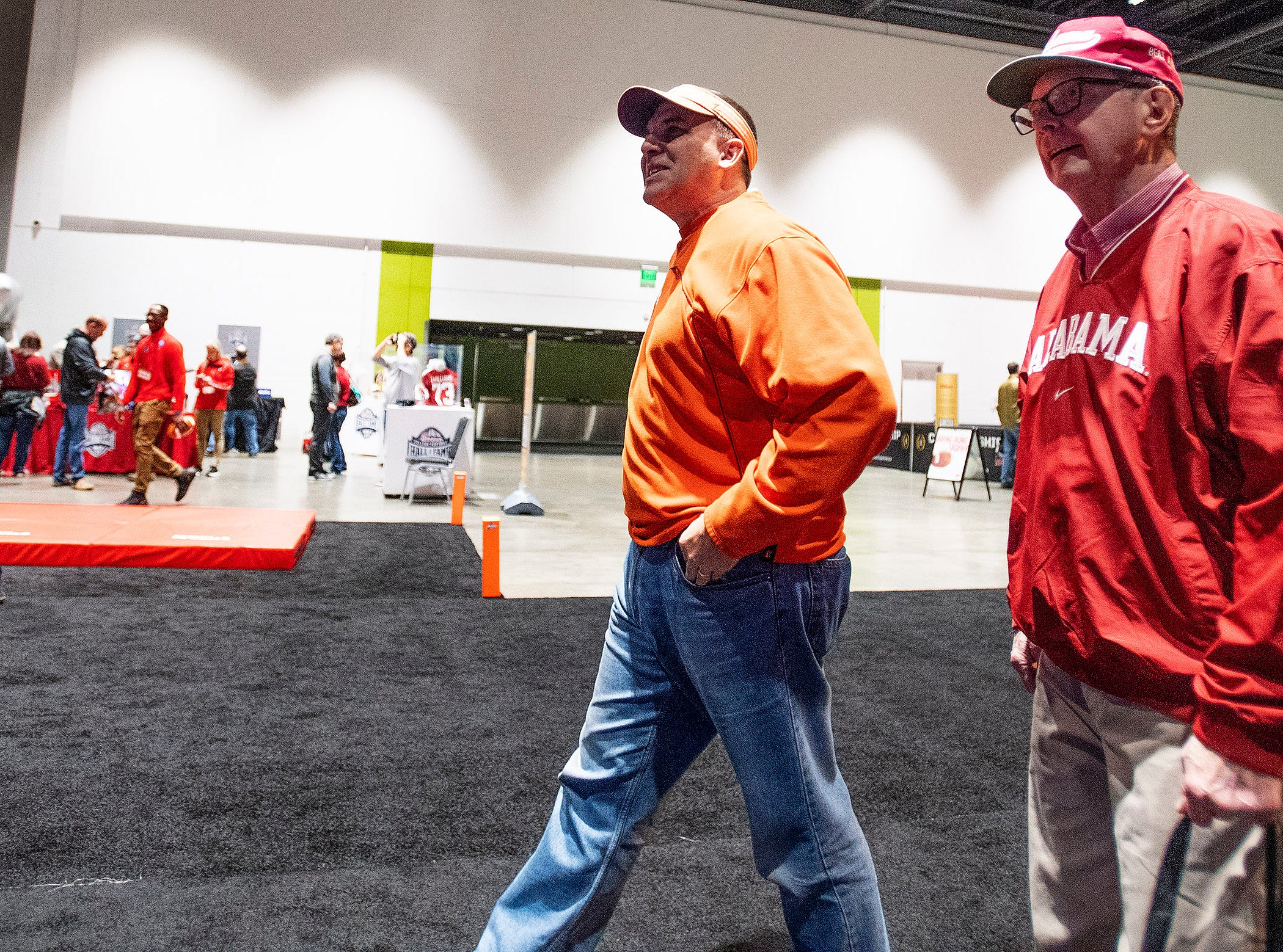 Clemson fan Glen Adair, left, and his Alabama fan father Charles Edgar walk through the Playoff Fan Central at the College Football National Championship in San Jose, Ca., on Sunday January 6, 2019.