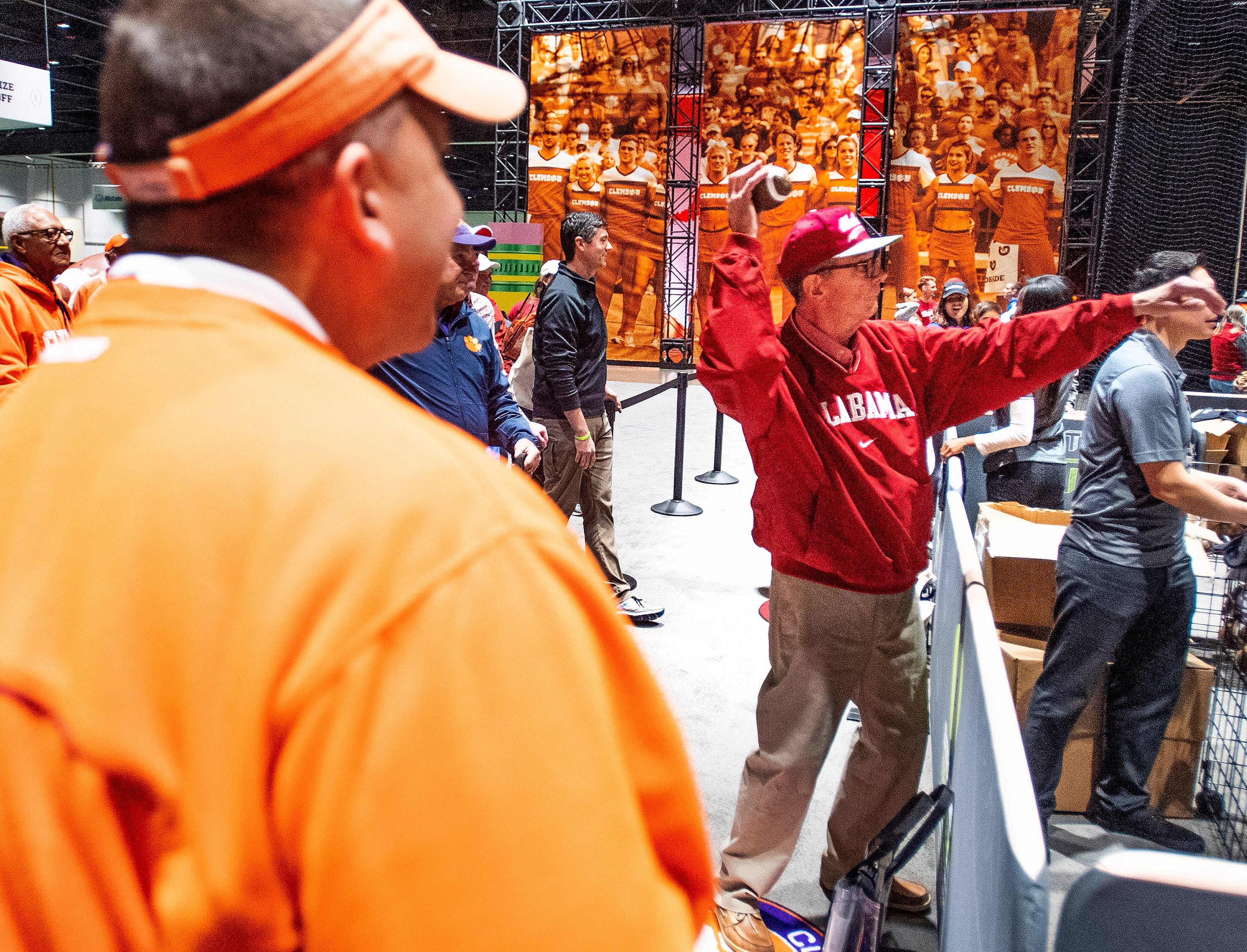 Clemson fan Glen Adair, left, watches his Alabama fan father Charles Edgar throw a ball at the Playoff Fan Central at the College Football National Championship in San Jose, Ca., on Sunday January 6, 2019.