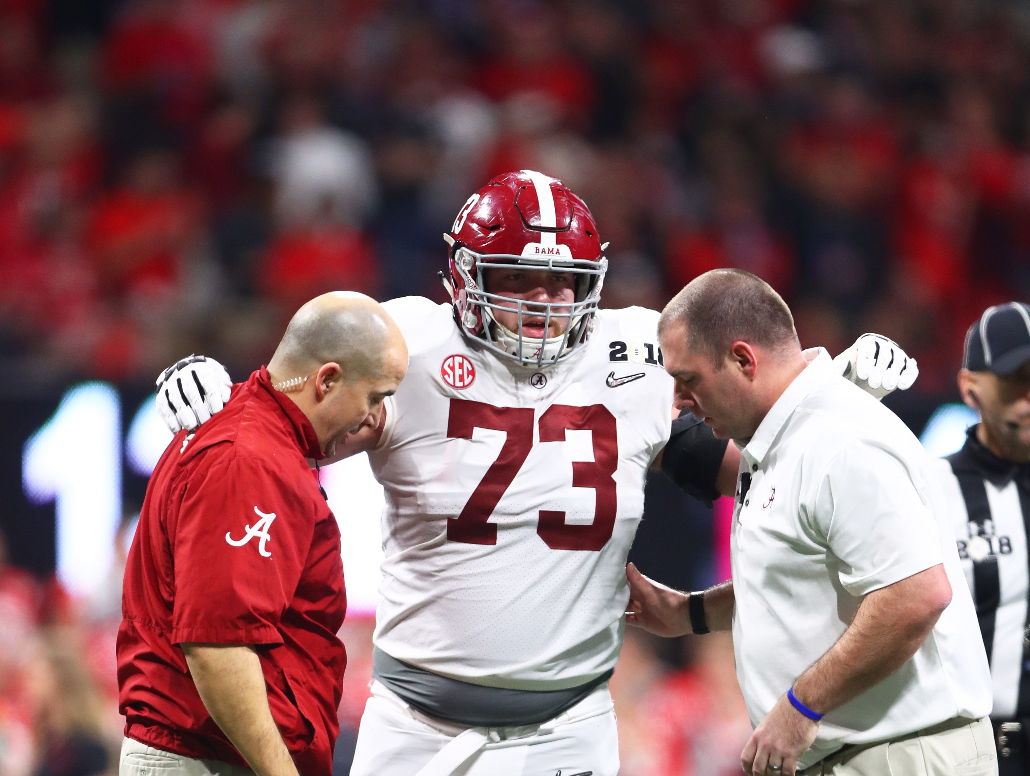 Jan 8, 2018; Atlanta, GA, USA; Trainers tend to Alabama Crimson Tide offensive lineman Jonah Williams (73) against the Georgia Bulldogs in the 2018 CFP national championship college football game at Mercedes-Benz Stadium. Mandatory Credit: Mark J. Rebilas-USA TODAY Sports