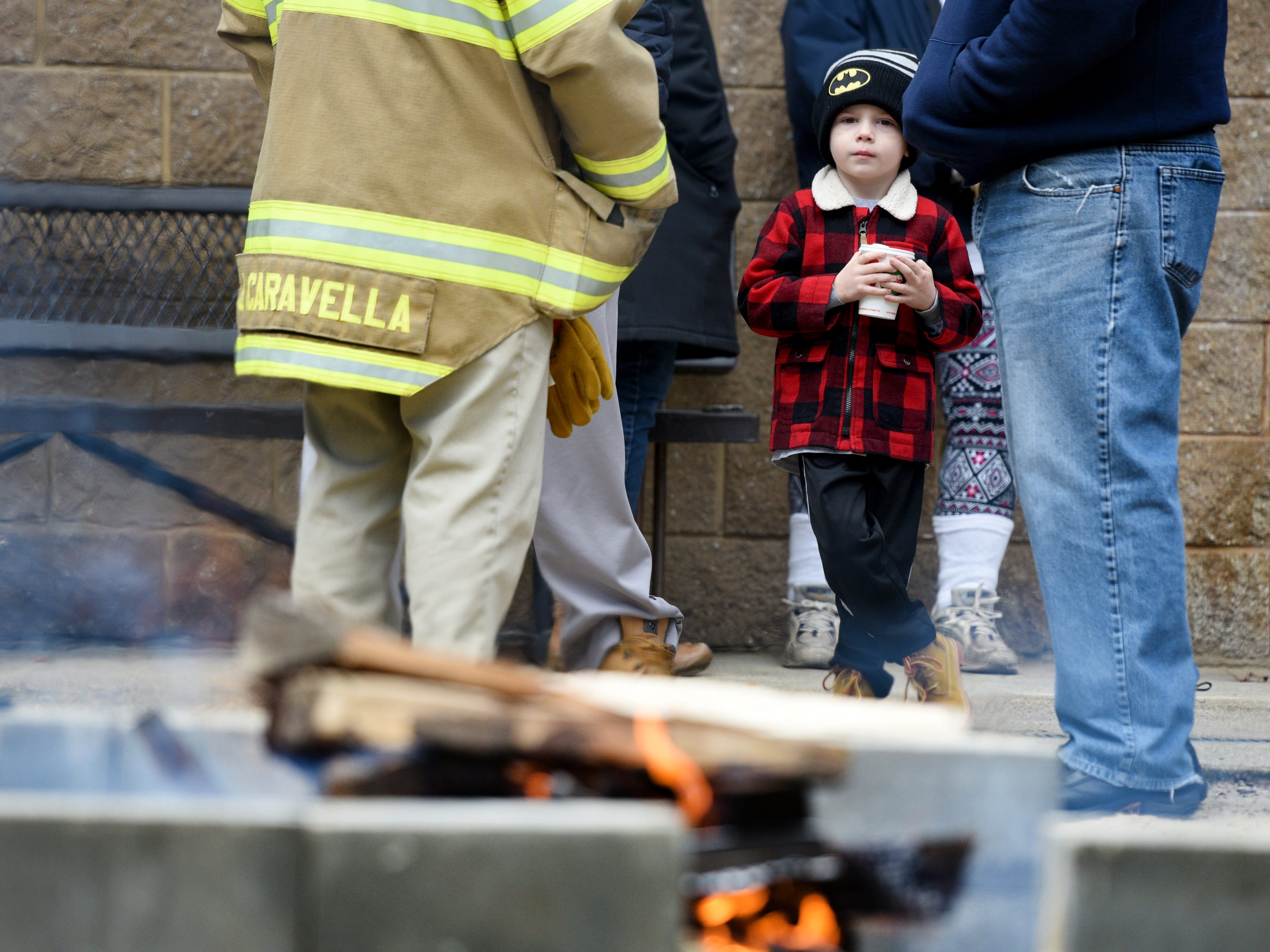 Jameson English, 4, keeps warm by the fire, with a hot chocolate, waiting to watch the 4th annual Pequannock Polar Plunge in Pequannock Valley Park on Sunday, January 6, 2019.