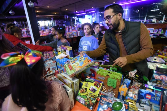 Councilman Salim Patel hands out toys during the 10th annual Three Kings Day celebration at Fiesta Night Club in Passaic on 01/06/19.