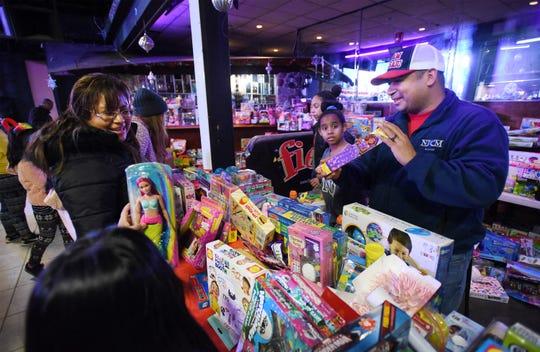 Passaic Mayor Hector Lora hands out toys during the 10th annual Three Kings Day celebration at Fiesta Night Club in Passaic on 01/06/19.