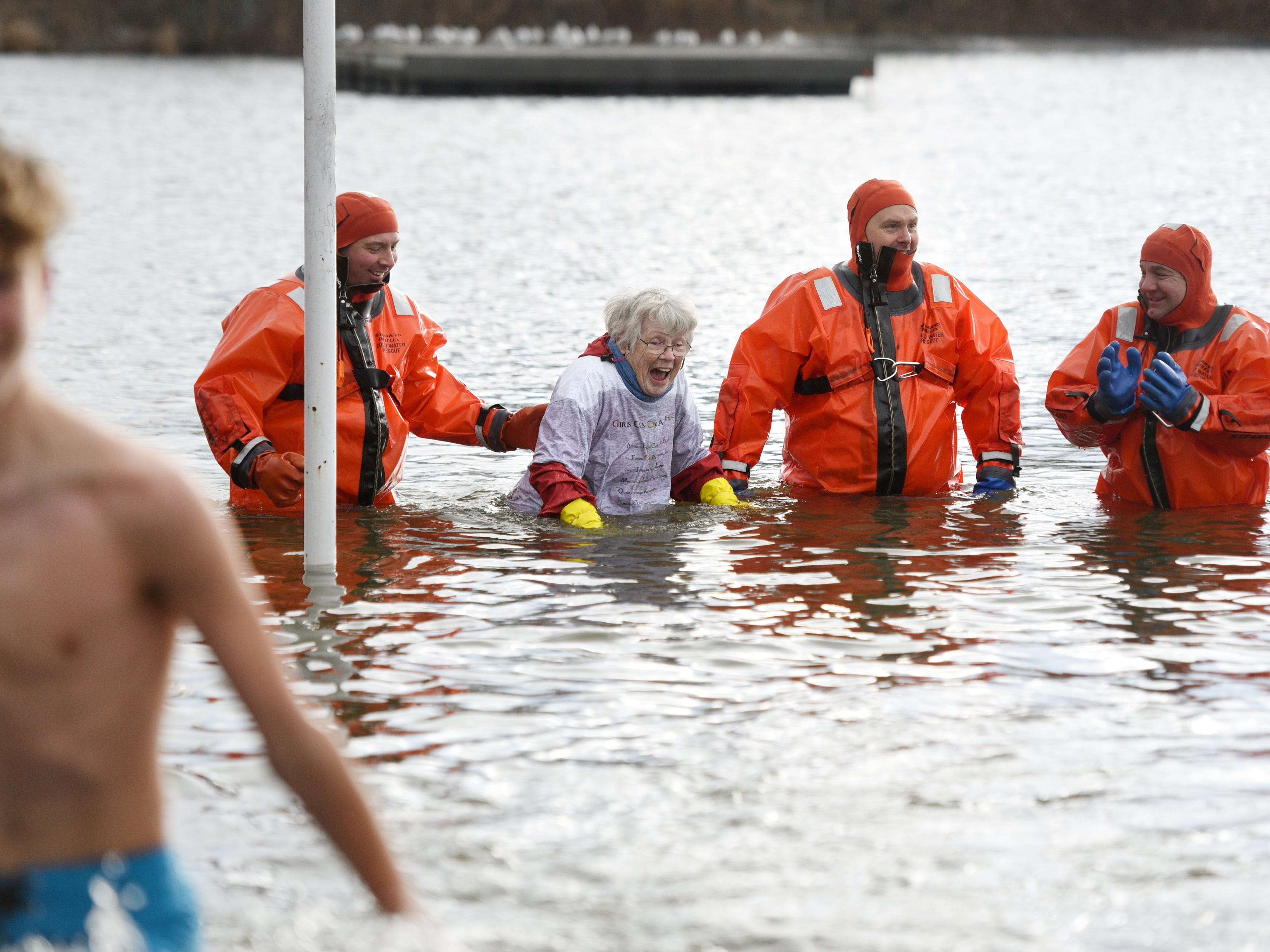 Kay Collins, 82, the oldest participant in the 4th annual Pequannock Polar Plunge, went the deepest into the lake at Pequannock Valley Park on Sunday, January 6, 2019. Collins circled the pole before dunking three times into the lake, where members of Pequannock Fire Department Engine Company One cheered her on.