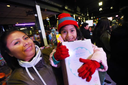Isabella Tapia (age 4) shows the toy that she received as she is held by her mother during the 10th annual Three Kings Day celebration at Fiesta Night Club in Passaic on 01/06/19.