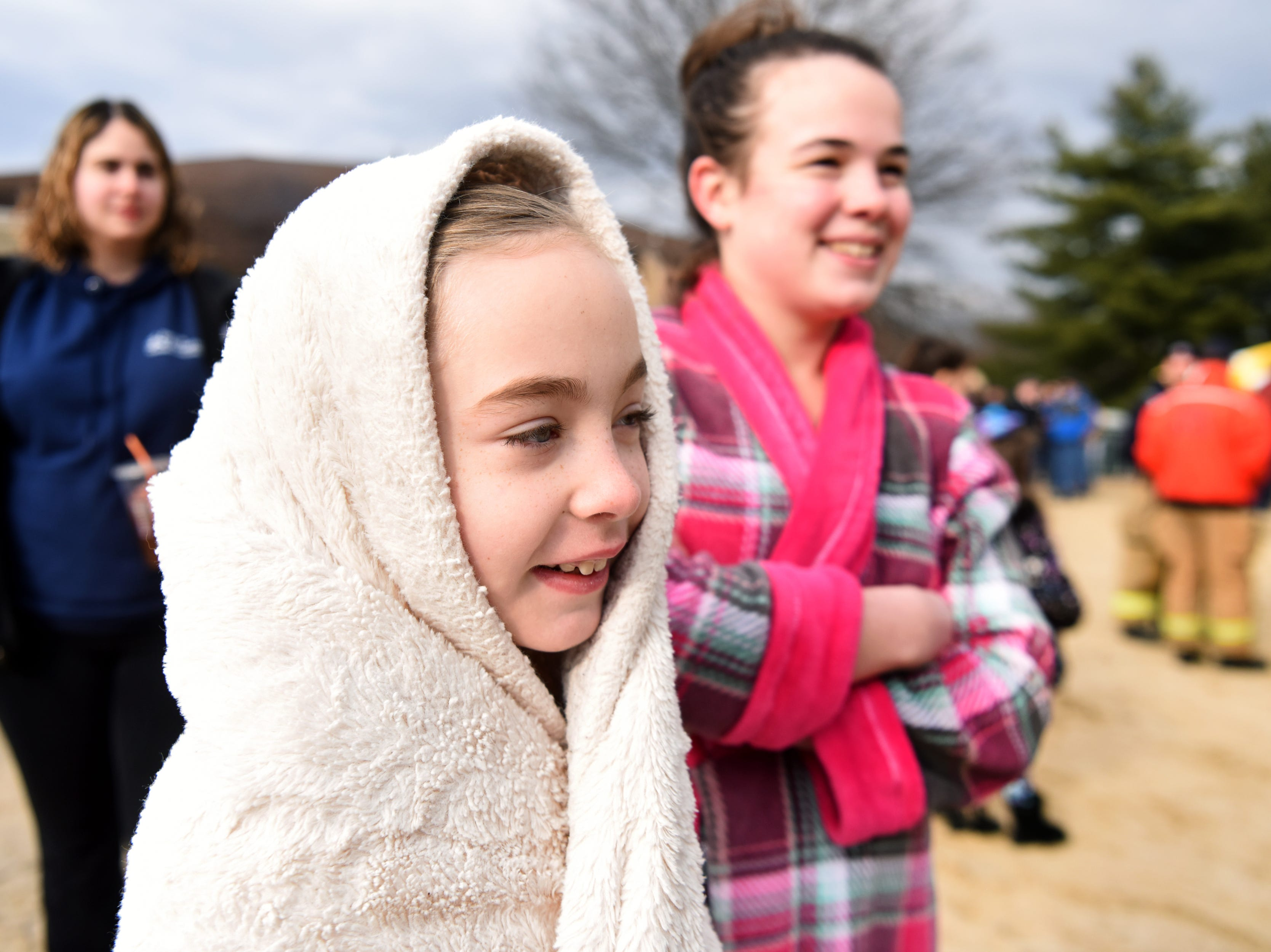 Brianna Carson, 8, huddles in her towel waiting for the start of the 4th annual Pequannock Polar Plunge in Pequannock Valley Park on Sunday, January 6, 2019.