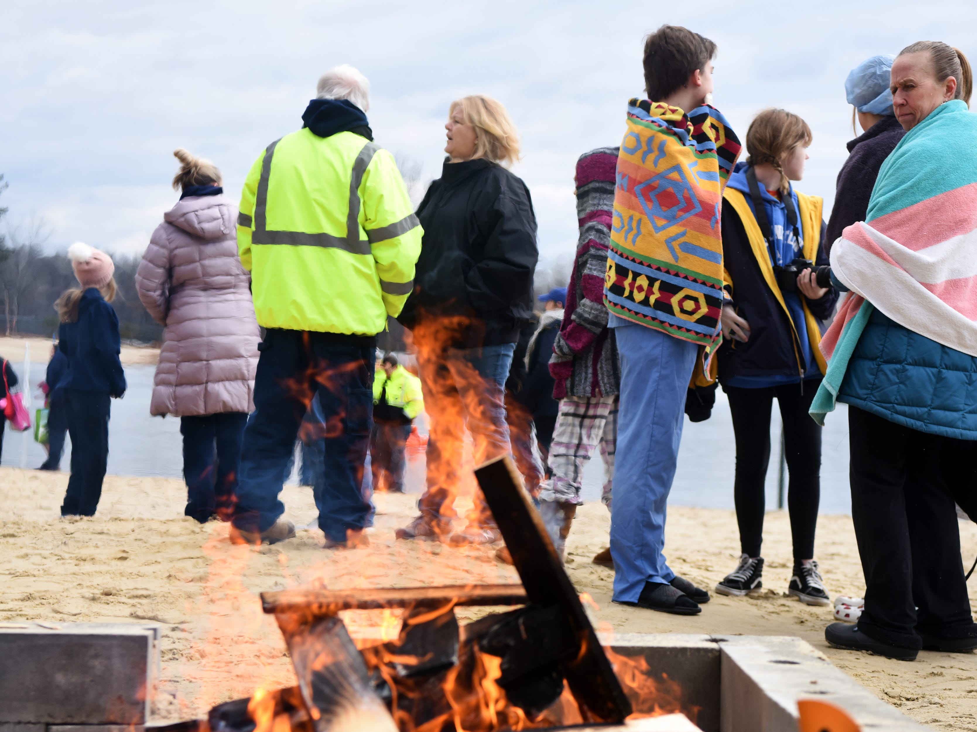 Participants in the 4th annual Pequannock Polar Plunge stay warm by the fire prior to jumping into the lake in Pequannock Valley Park on Sunday, January 6, 2019.