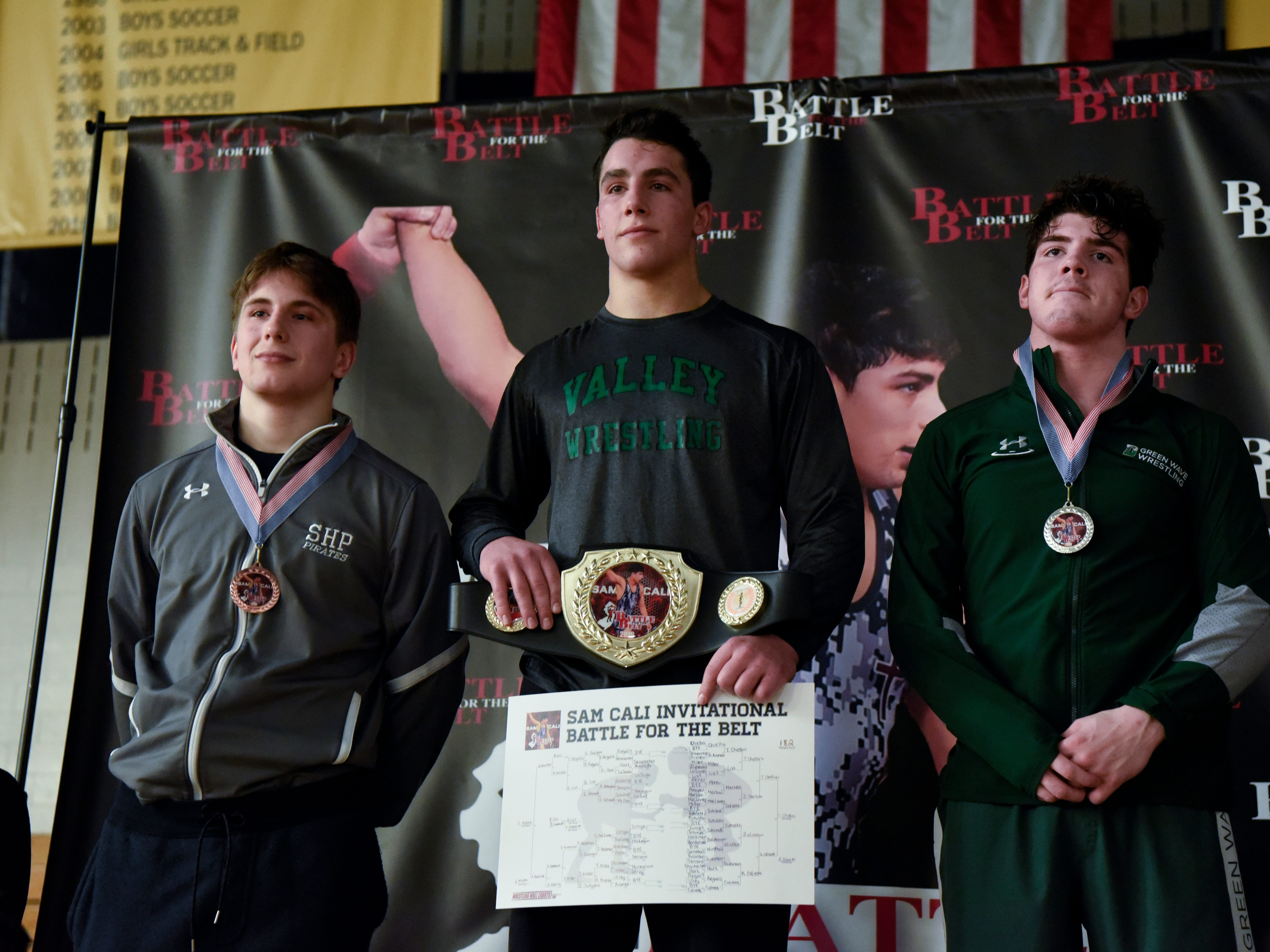 Tommy Chiellini of Pascack Valley, center, poses with the belt after winning his 182-pound final during the Sam Cali Battle for the Belt on Sunday, Jan. 6, 2019, in West Orange.