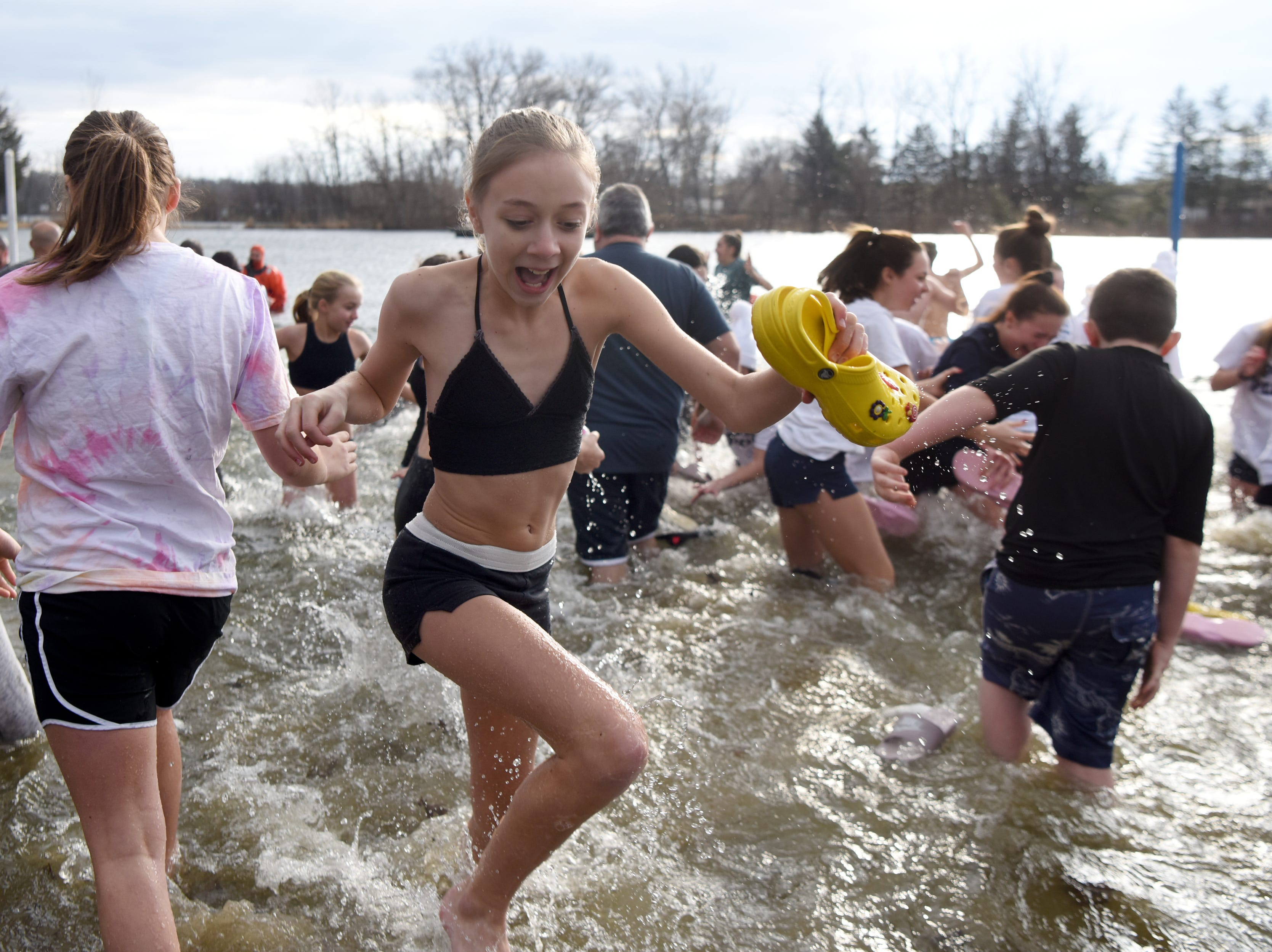 Participants in the 4th annual Pequannock Polar Plunge rush out of the lake in Pequannock Valley Park on Sunday, January 6, 2019.