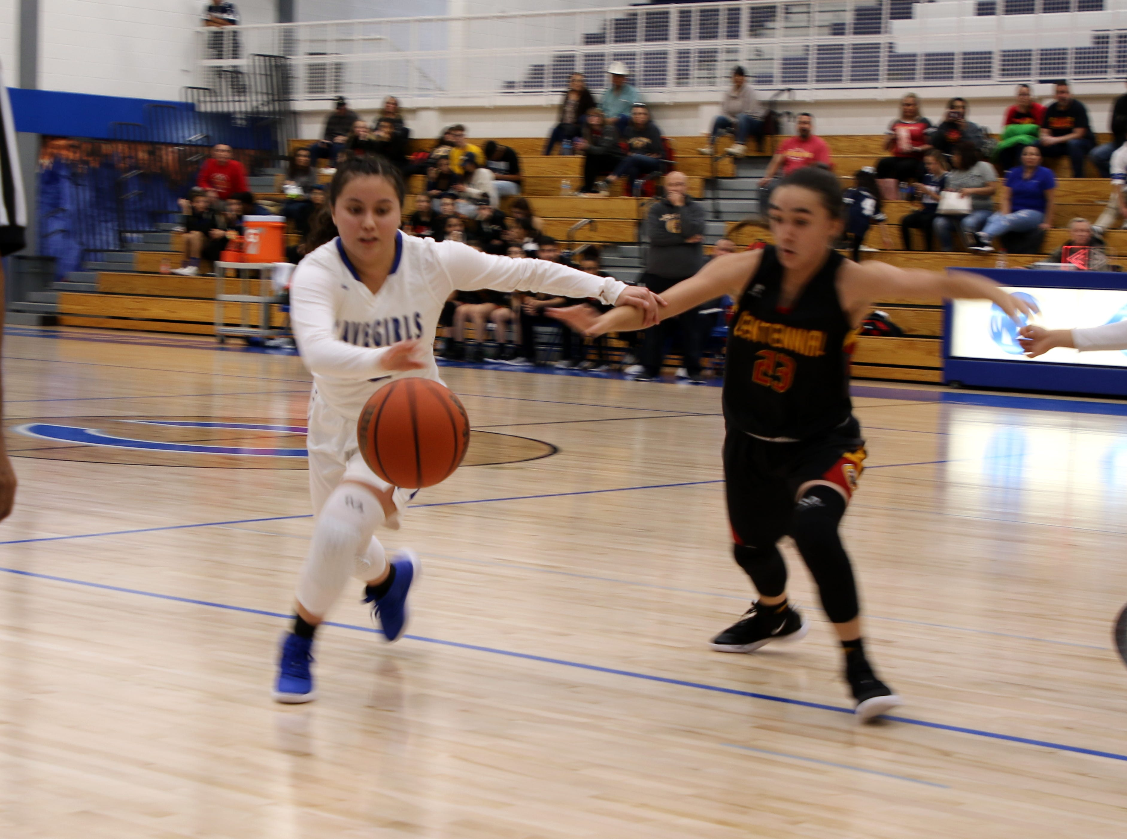 Carlsbad's Nyah Chacon and Centennial's Andreana Armendariz (23) fight for a loose ball during Saturday's game.
