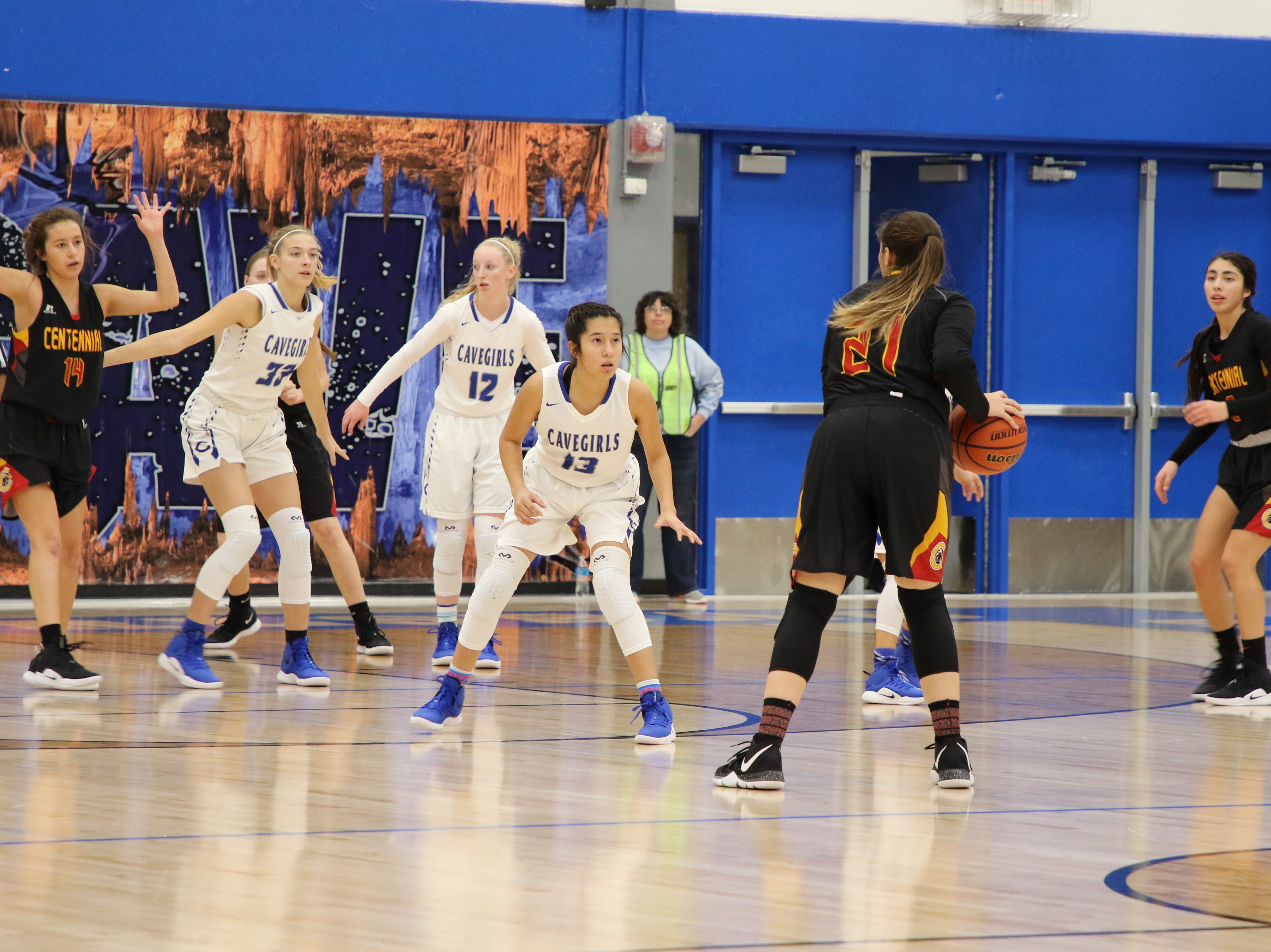 Dianne Hefner looks to pass while Tori Flores (13) guards her.