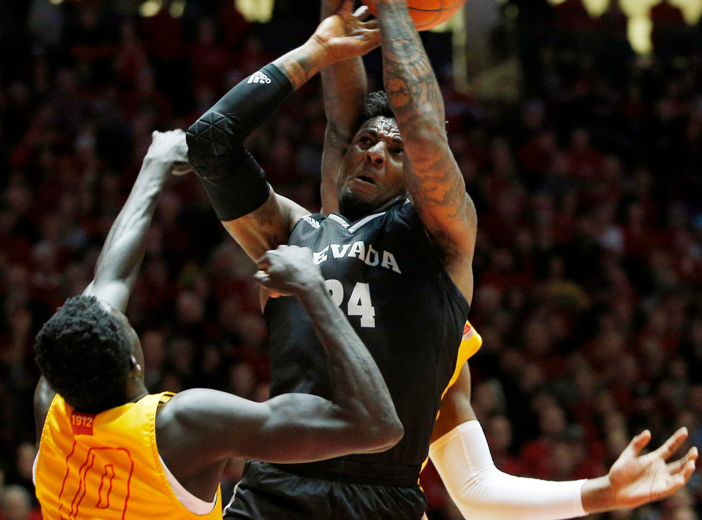 Nevada forward Jordan Caroline, center, is fouled by New Mexico's Carlton Bragg, obscured, as New Mexico's Makuach Maluach (10), of Australia, looks on during the first half of an NCAA college basketball game in Albuquerque Saturday.