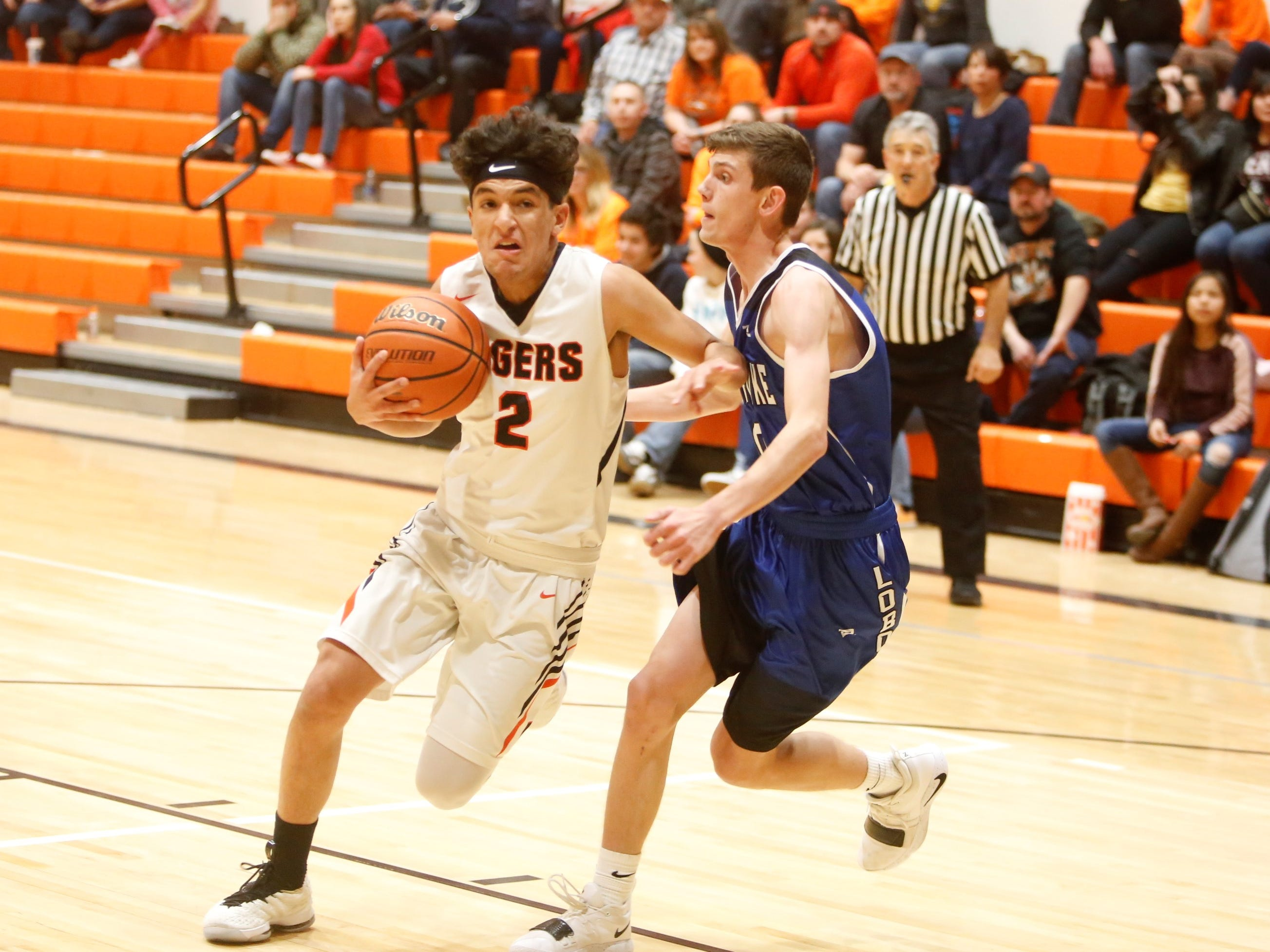 Aztec's Anthony Rios drives to the basket for a layup against Snowflake's Trever Willis during the Rumble in the Jungle tournament third place game Saturday at Lillywhite Gym in Aztec.