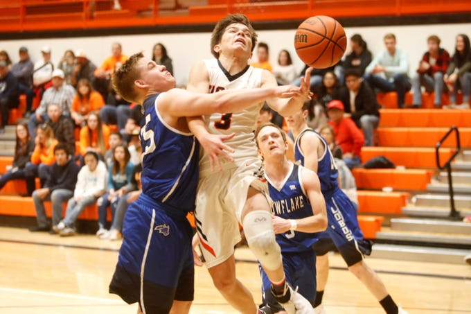 Aztec's Gabe Wood attacks the basket and gets fouled by Snowflake's David Brimhall during the Rumble in the Jungle tournament third place game at Lillywhite Gym in Aztec.