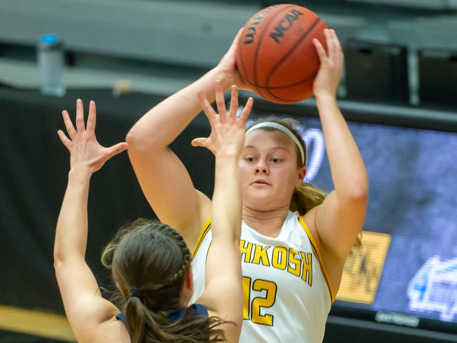 UW-Oshkosh's Leah Porath throws a pass over UW-Stout's Liz Oswald during a 2019 game at the Kolf Sports Center in Oshkosh.