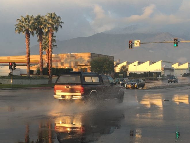 Traffic passes through a puddle of water on Gene Autry Trail at Ramon Road. As much as 0.25 inches of rain fell on parts of Palm Springs Sunday, weather experts say.