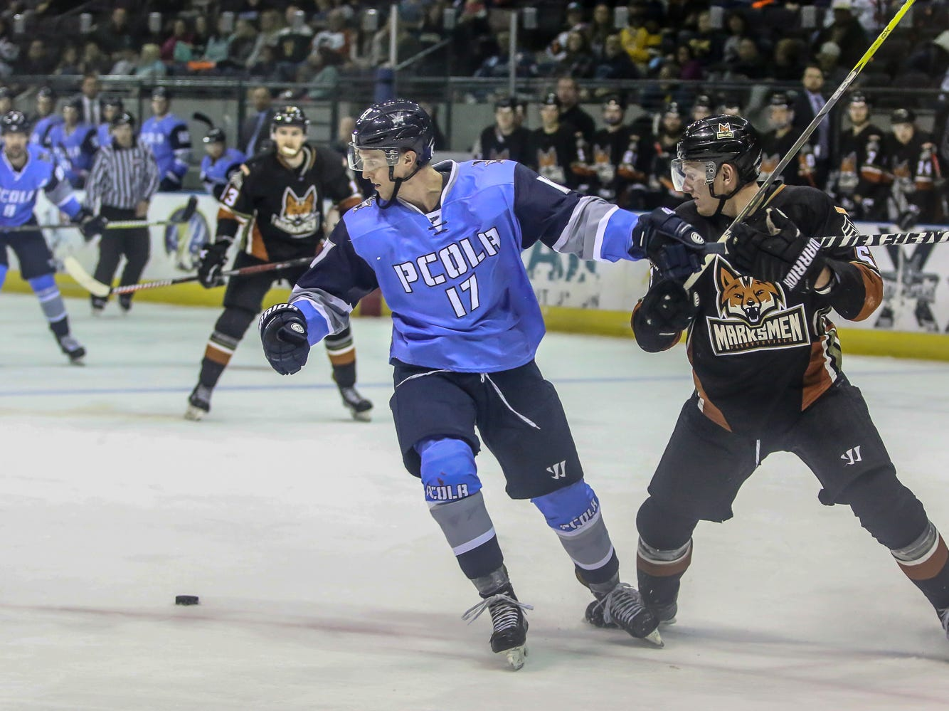 Pensacola's Brantley Sherwood (17) tries to get his stick out from the grip of Fayetteville's Alfred Johansson (5) as they move past the loose puck at the Pensacola Bay Center on Saturday, January 5, 2019.